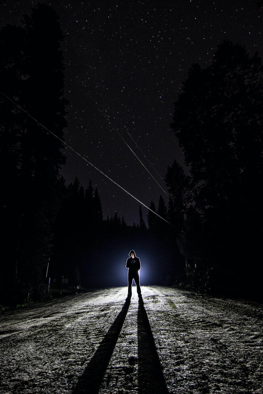 man standing on pathway during nighttime