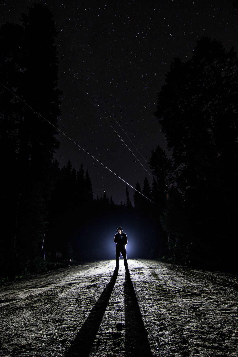 man standing on pathway during nighttime