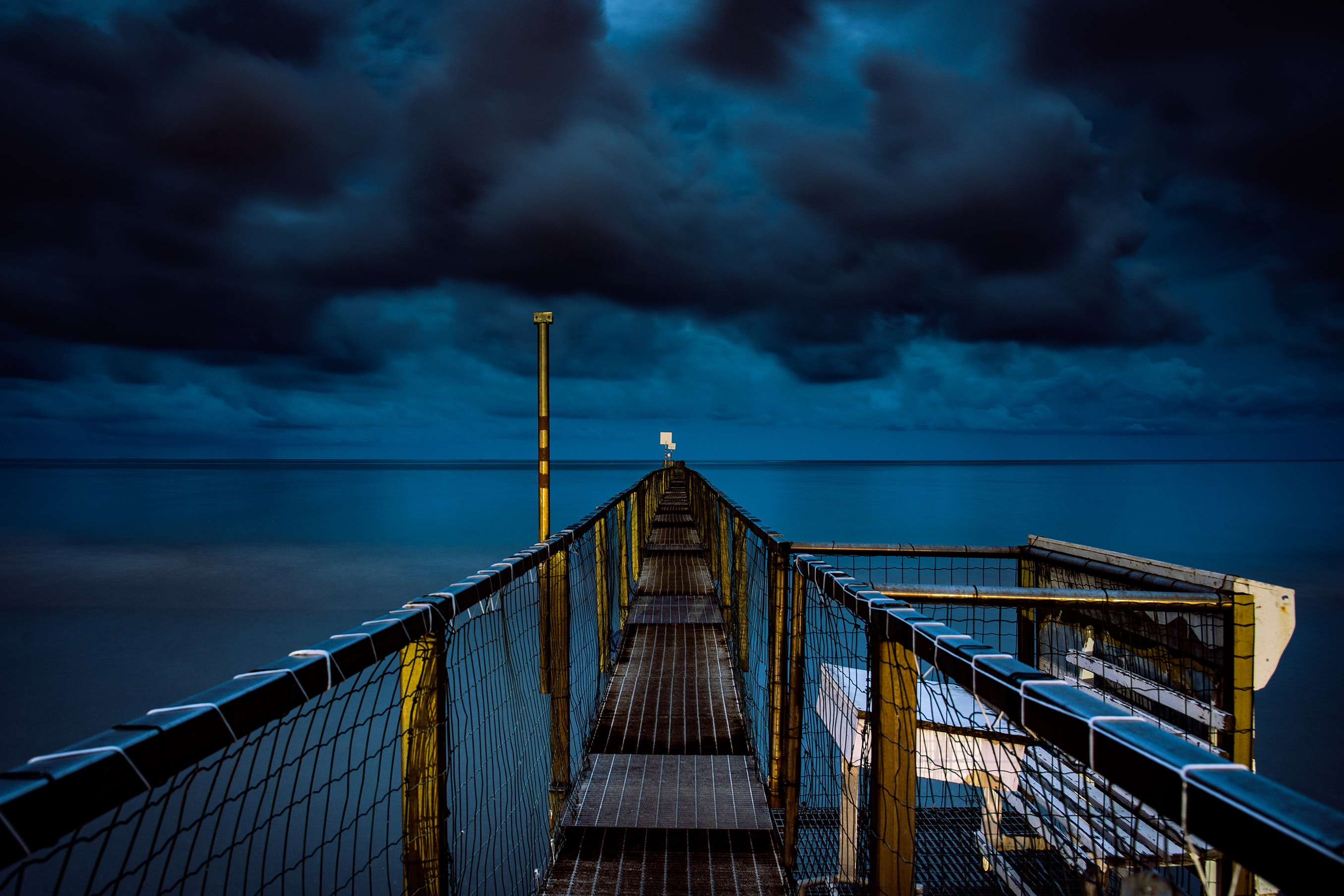 A dock that is lit up at night time over calm water in Rimini