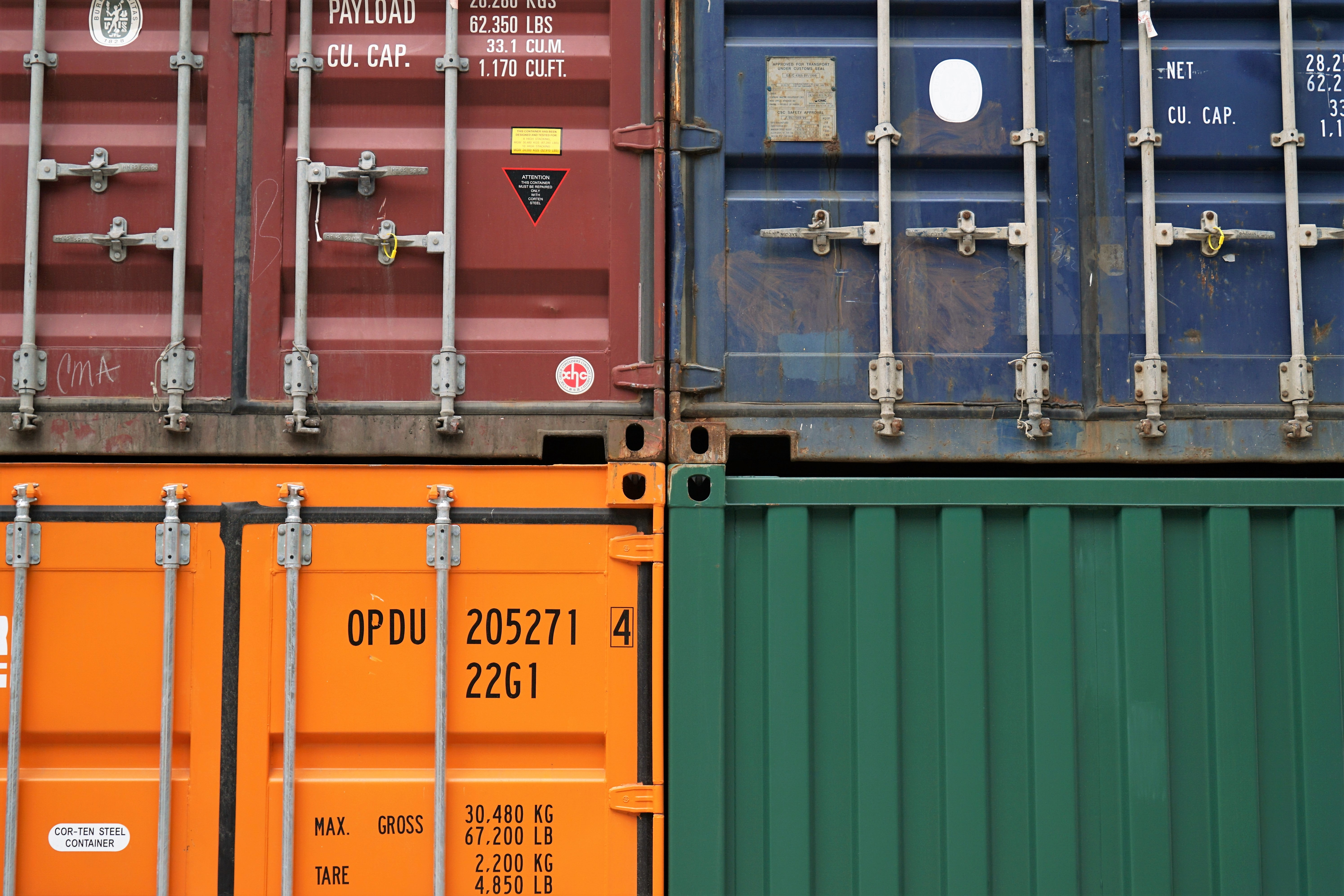 Close-up of four shipping containers in various colors stacked on top of each other