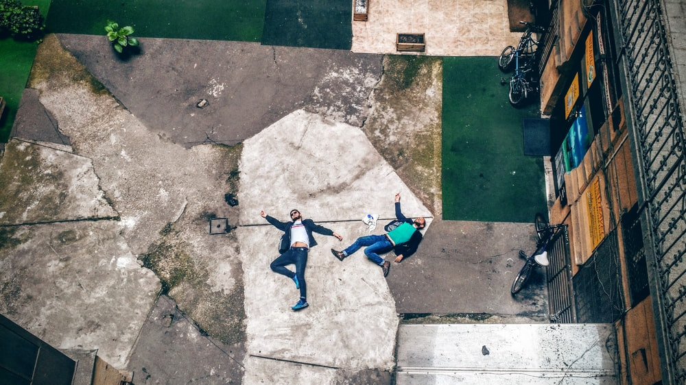 aerial view of two men lying on concrete pavement