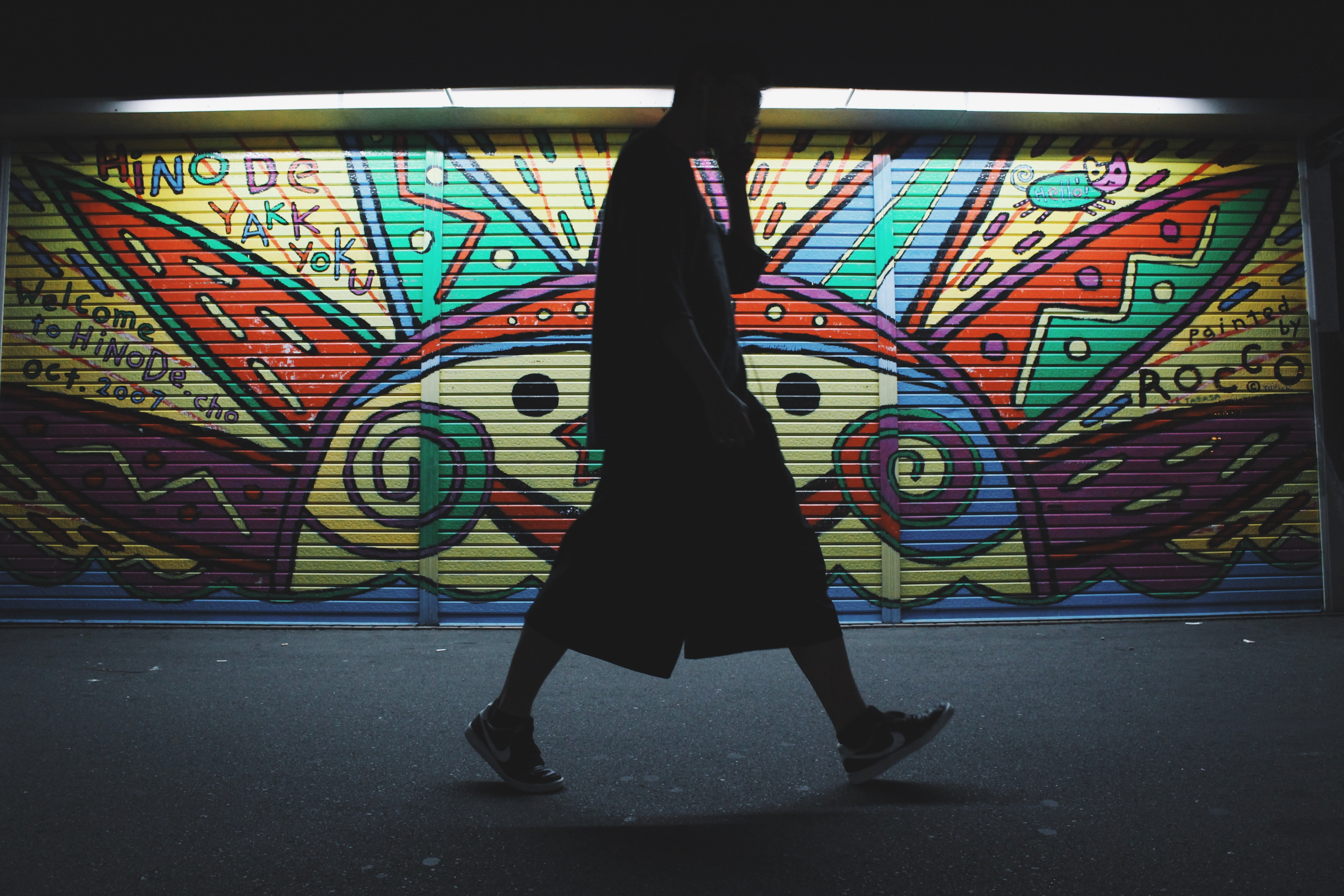 Silhouette of man in shorts and t shirt on phone walking past colorful sun graffiti art
