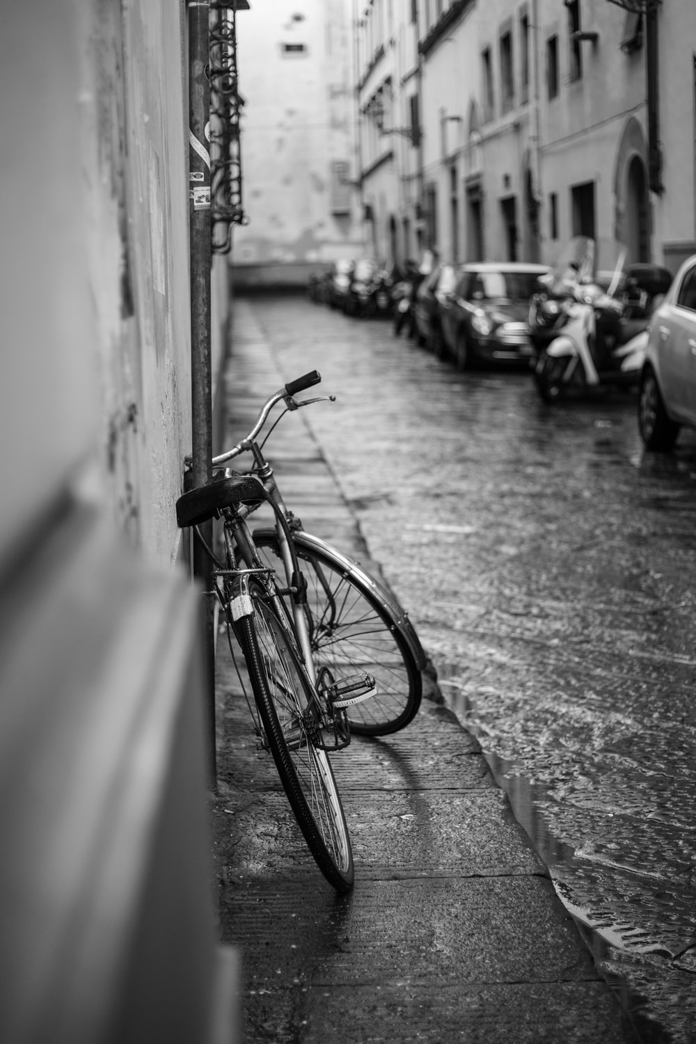 Grayscale photo of bike on wall