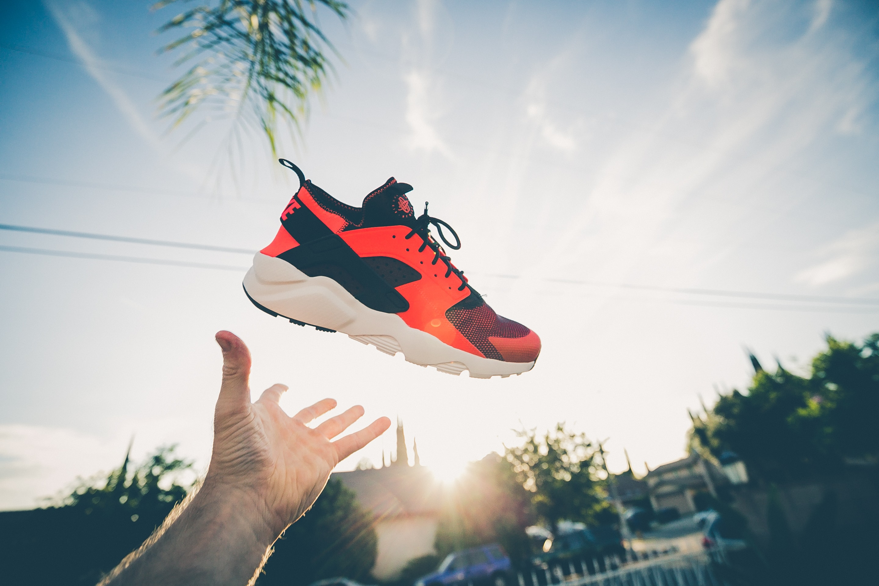 Man tossing red shoes up in the air from his hands