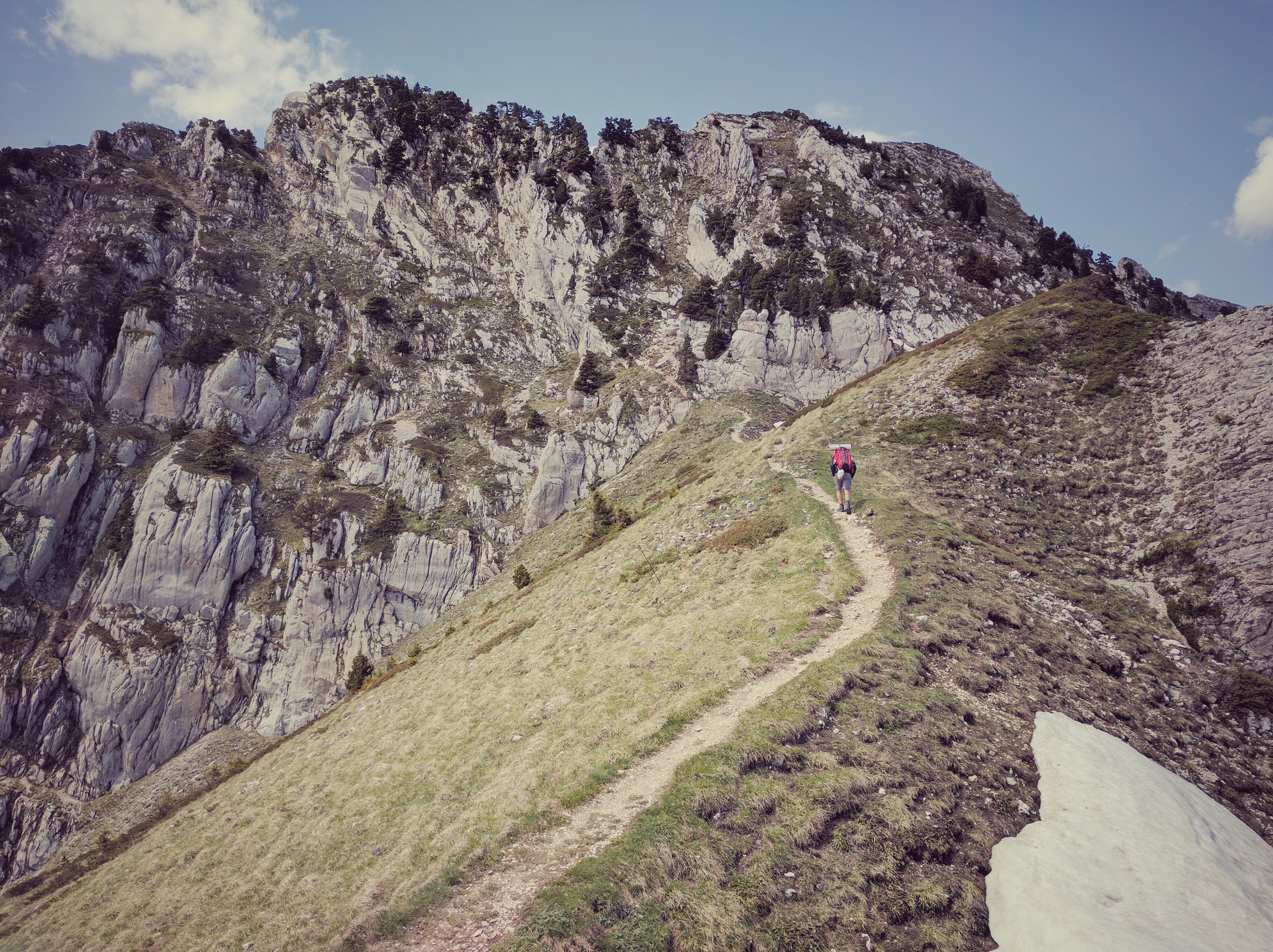 A person hiking up a steep trail along the side of a mountain in Grenoble