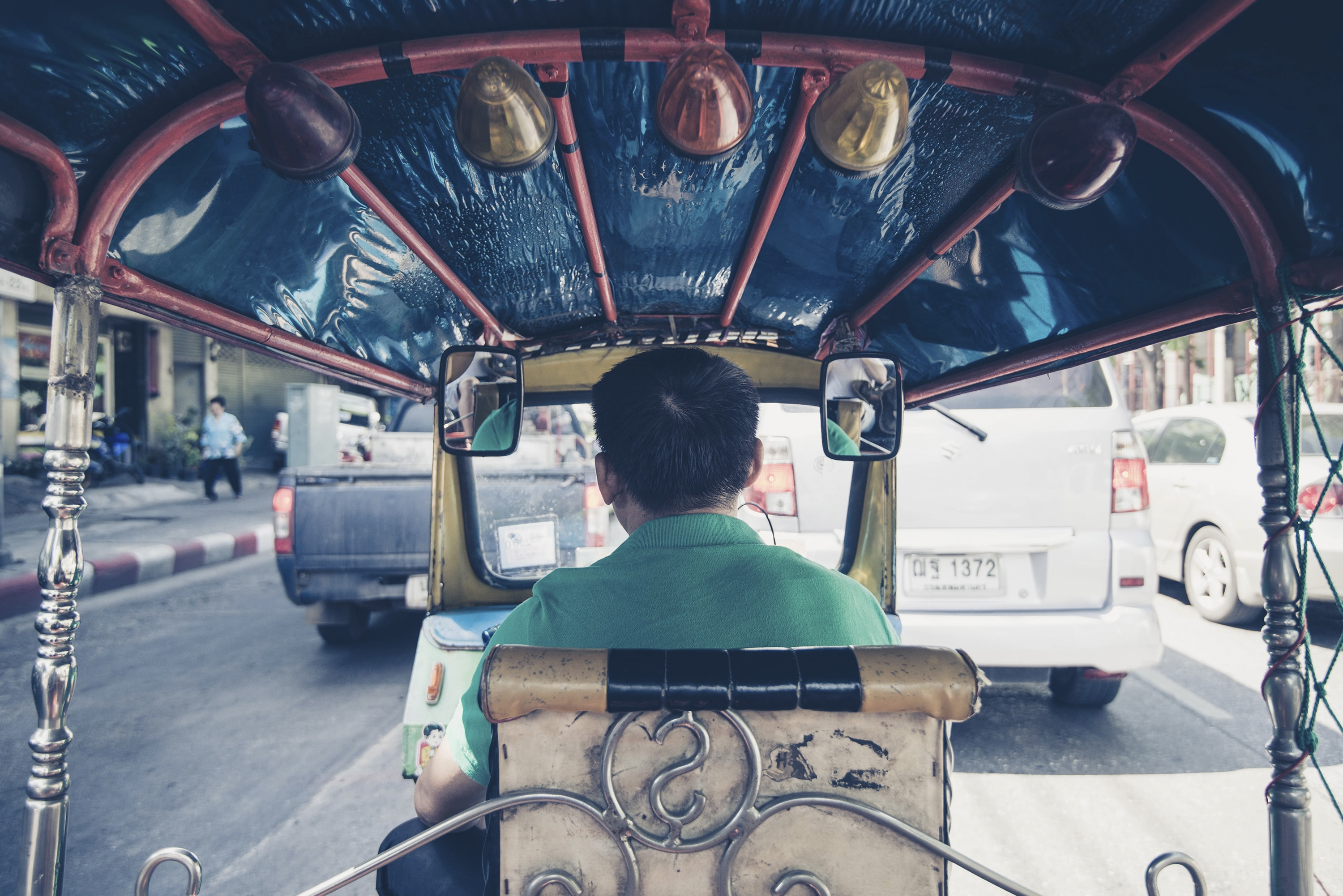 A view from the back seat of an auto rickshaw driving in the traffic