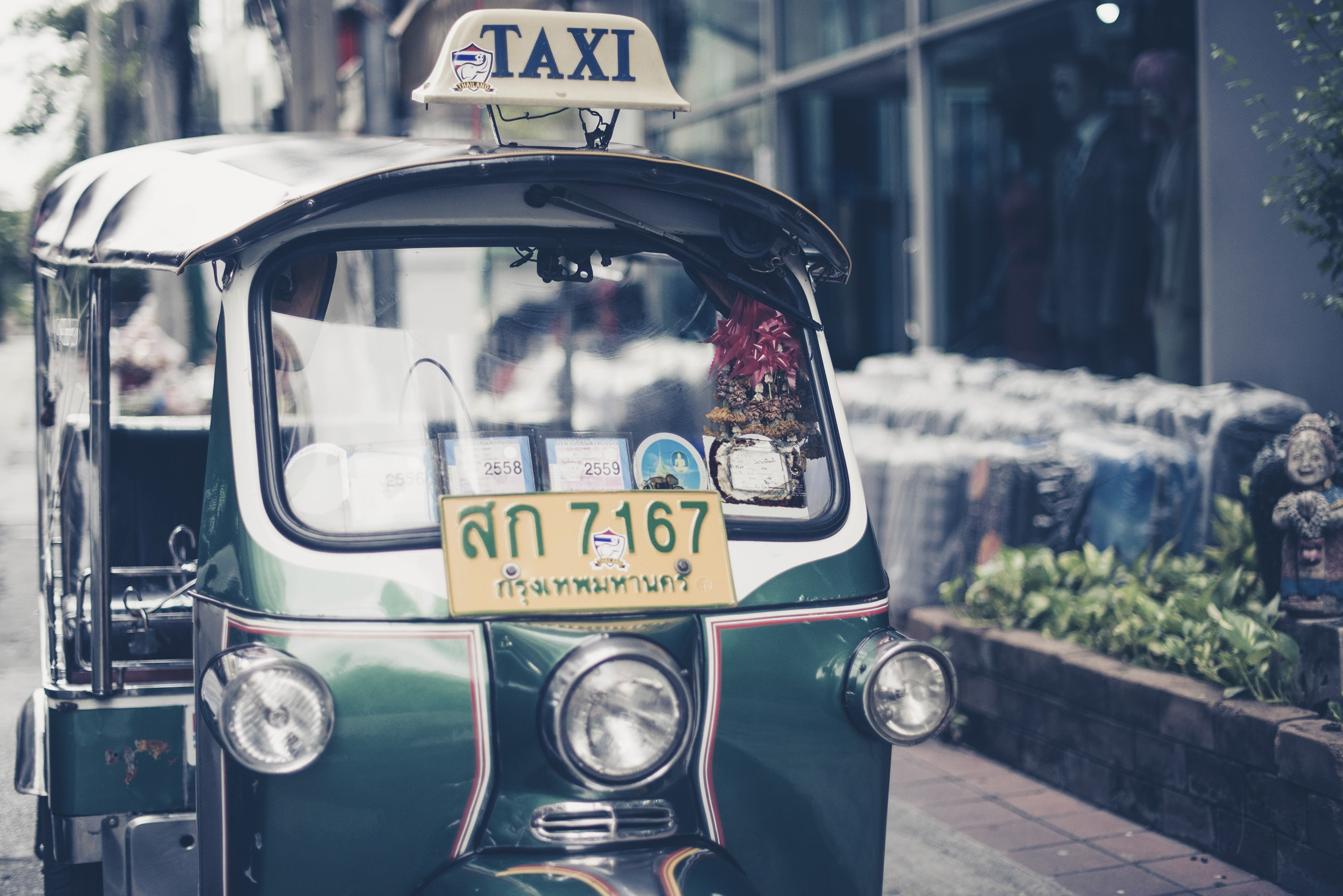 Green taxi in Bangkok with license plate on front sits outside of building near smiling statue