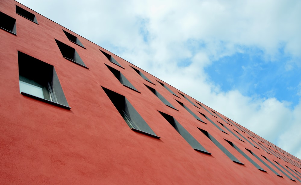 low-angle photography of red concrete building