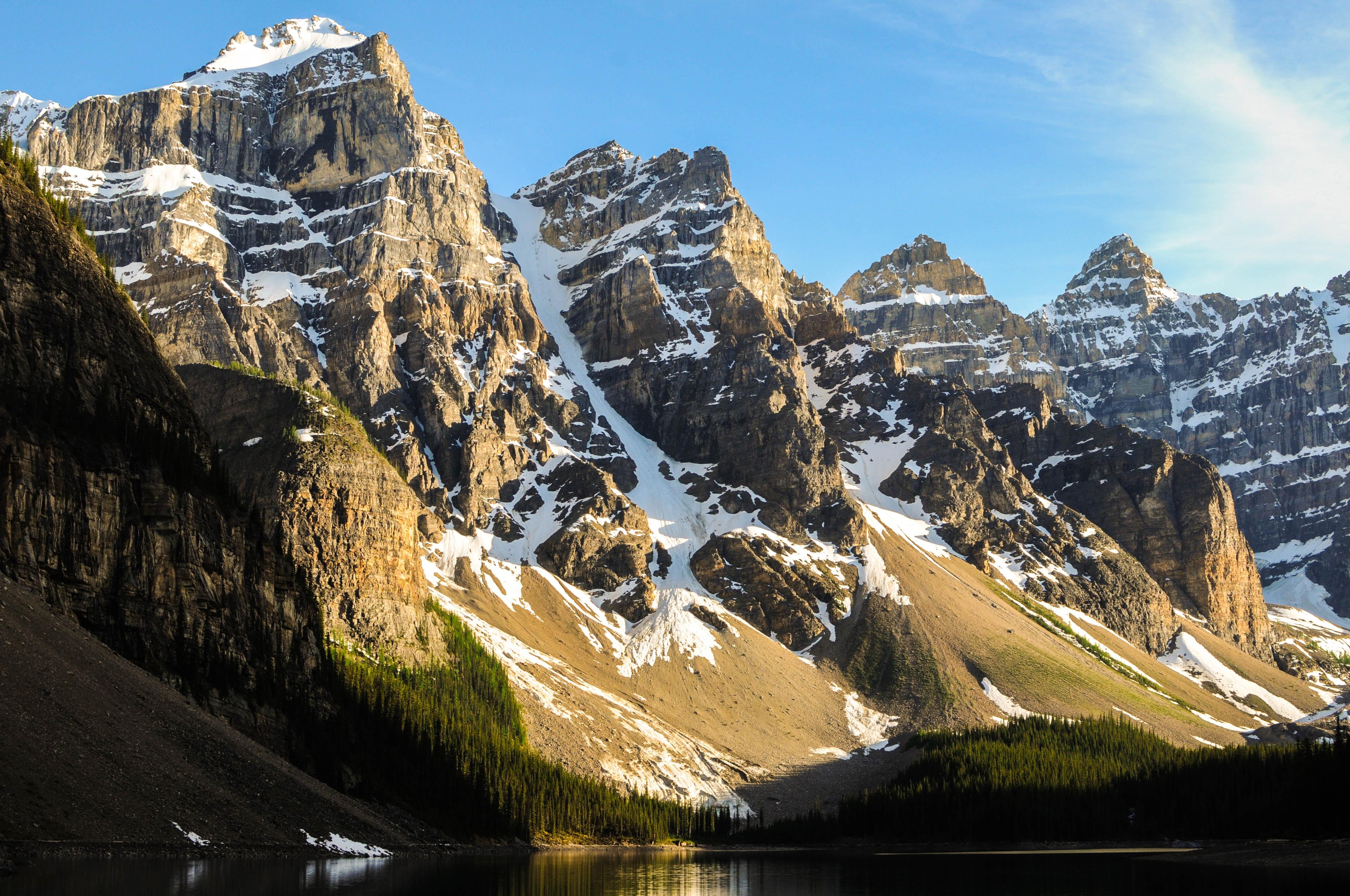 Snow covered mountain peaks next to Moraine Lake.
