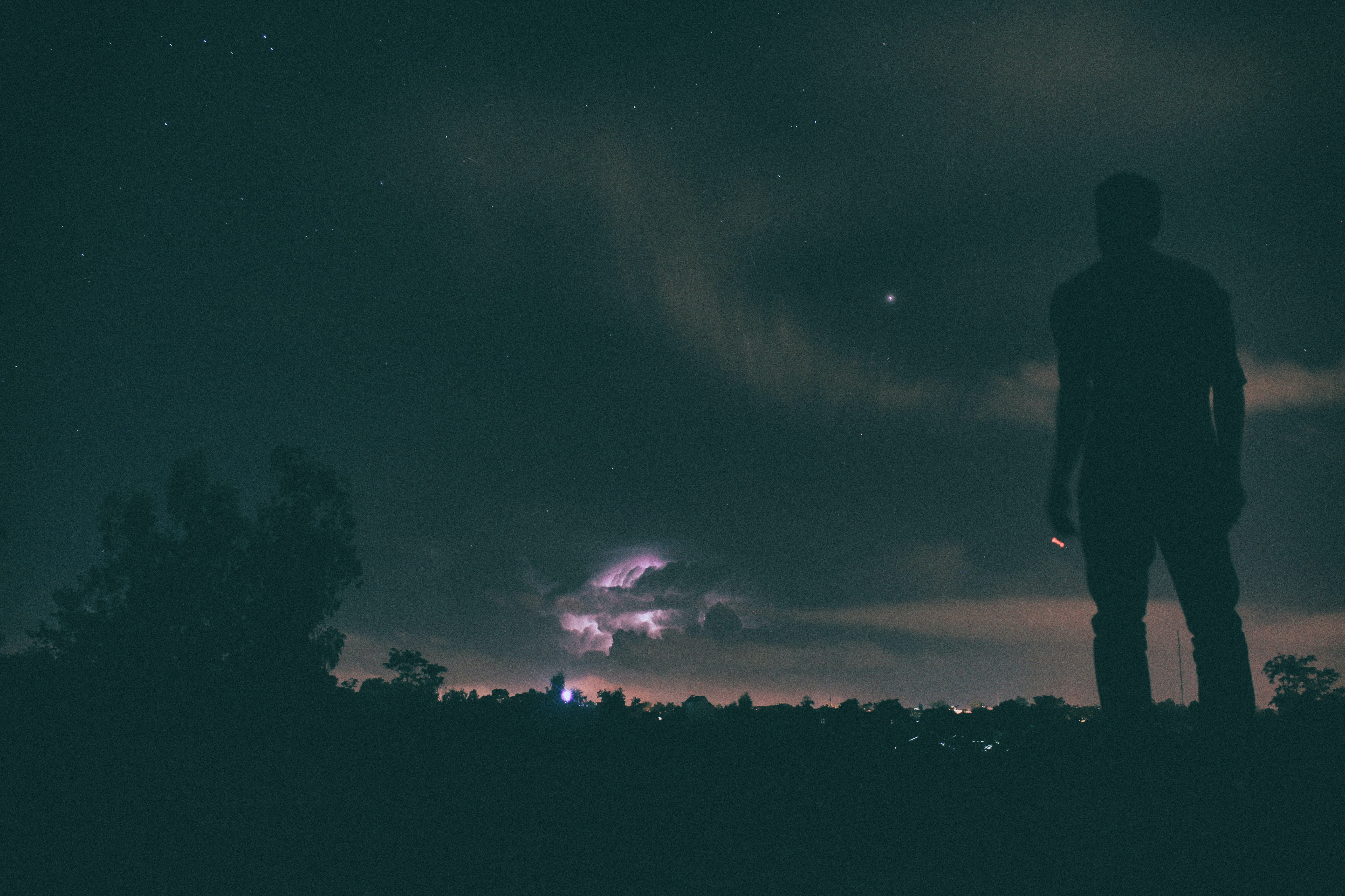 silhouette of man standing under night sky