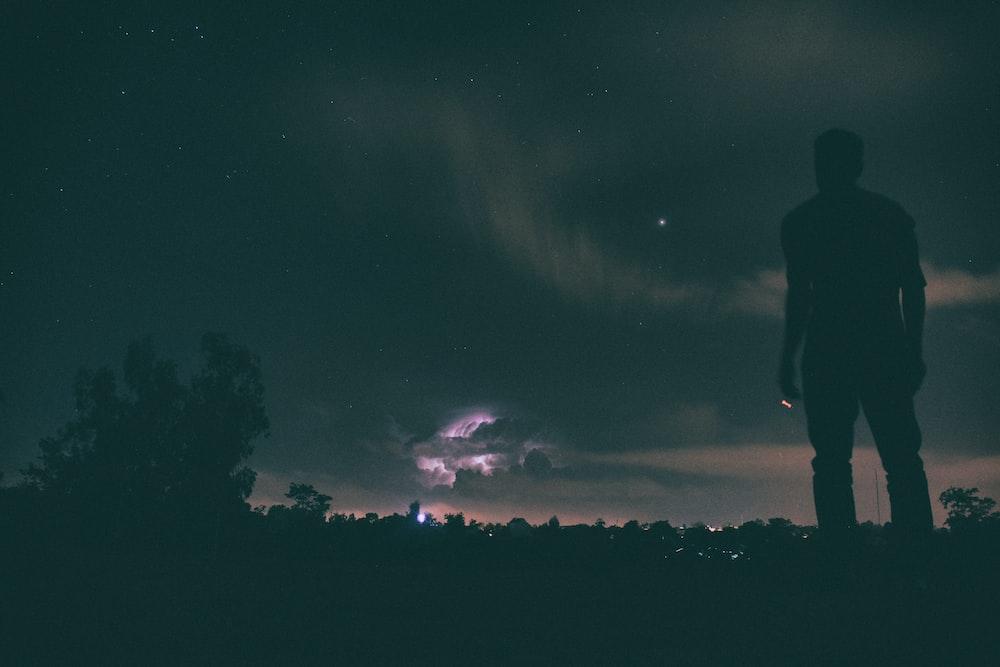 silhouette of man standing under night sky