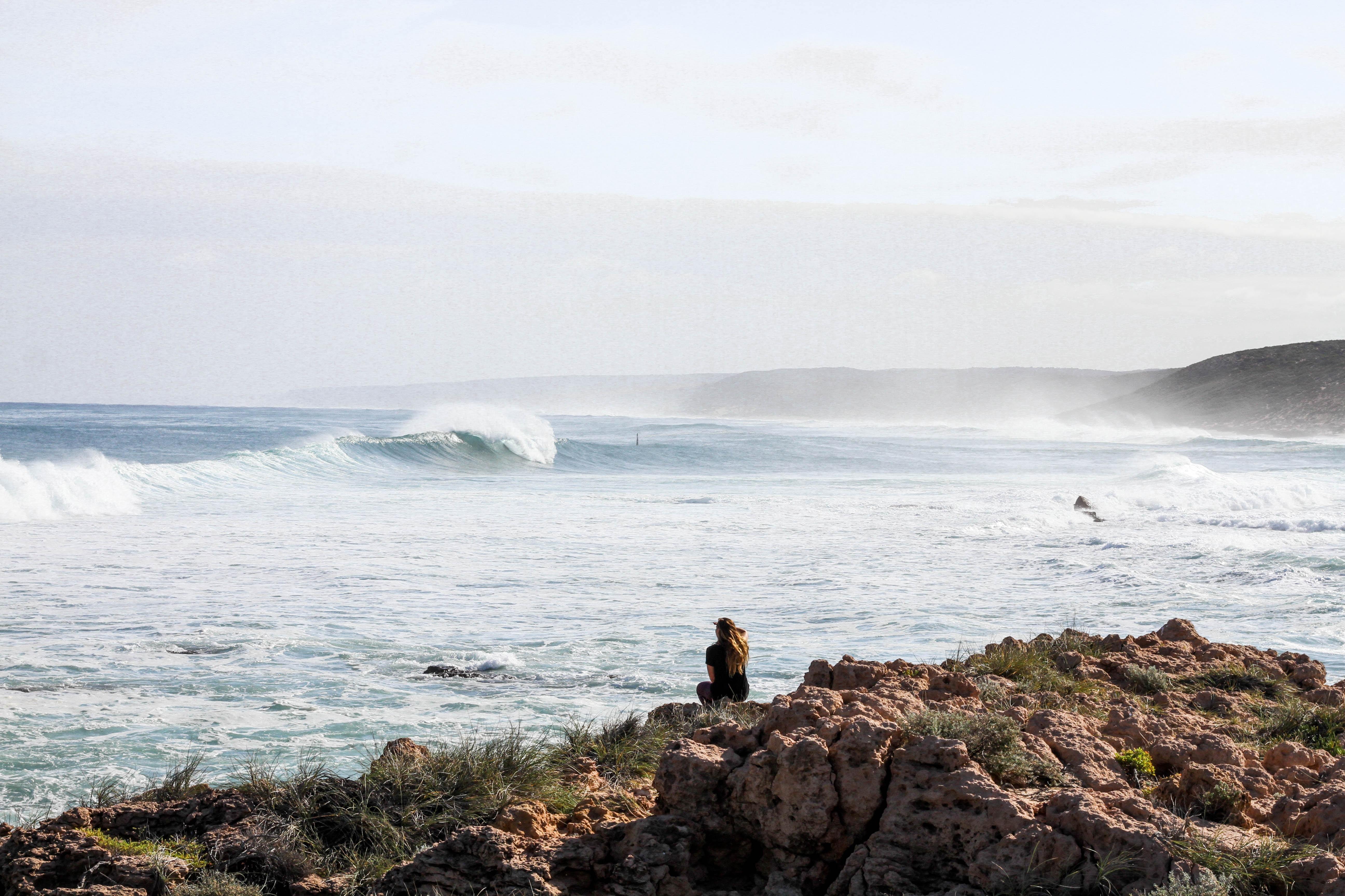 woman sitting on rock near the beach