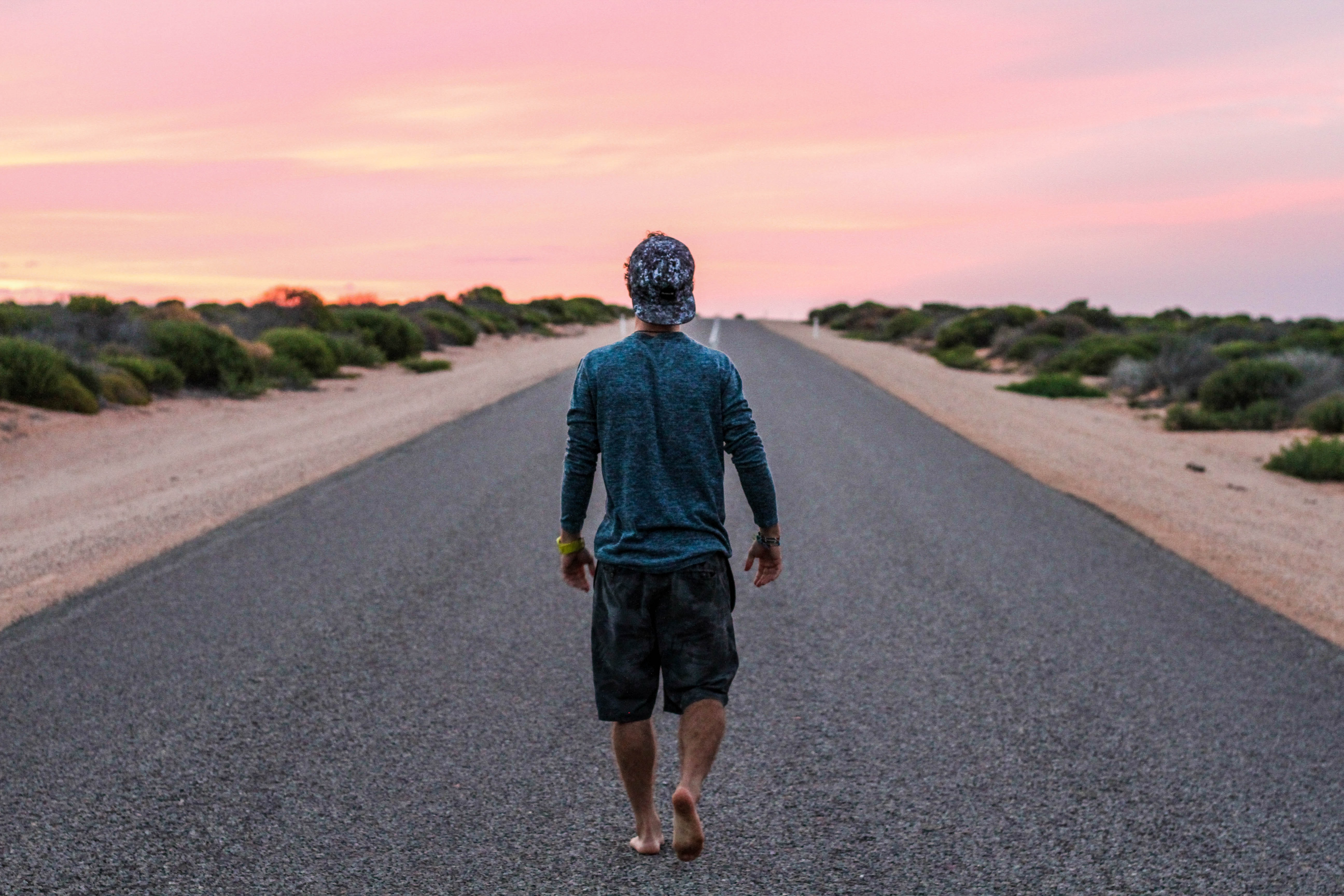 A barefoot man in a baseball hat walking on an empty asphalt road during sunset