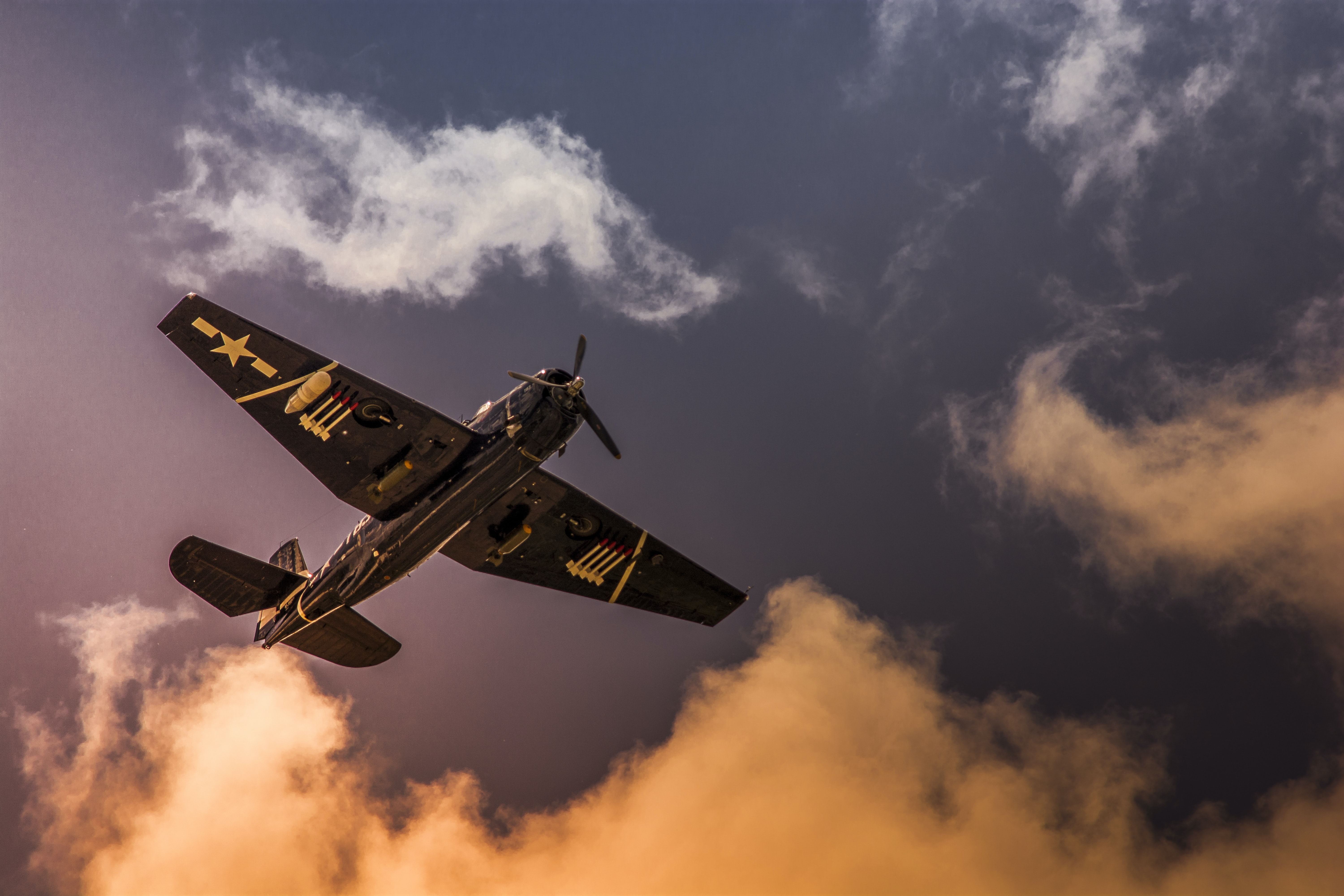 Ground view of an old war plane in the air.