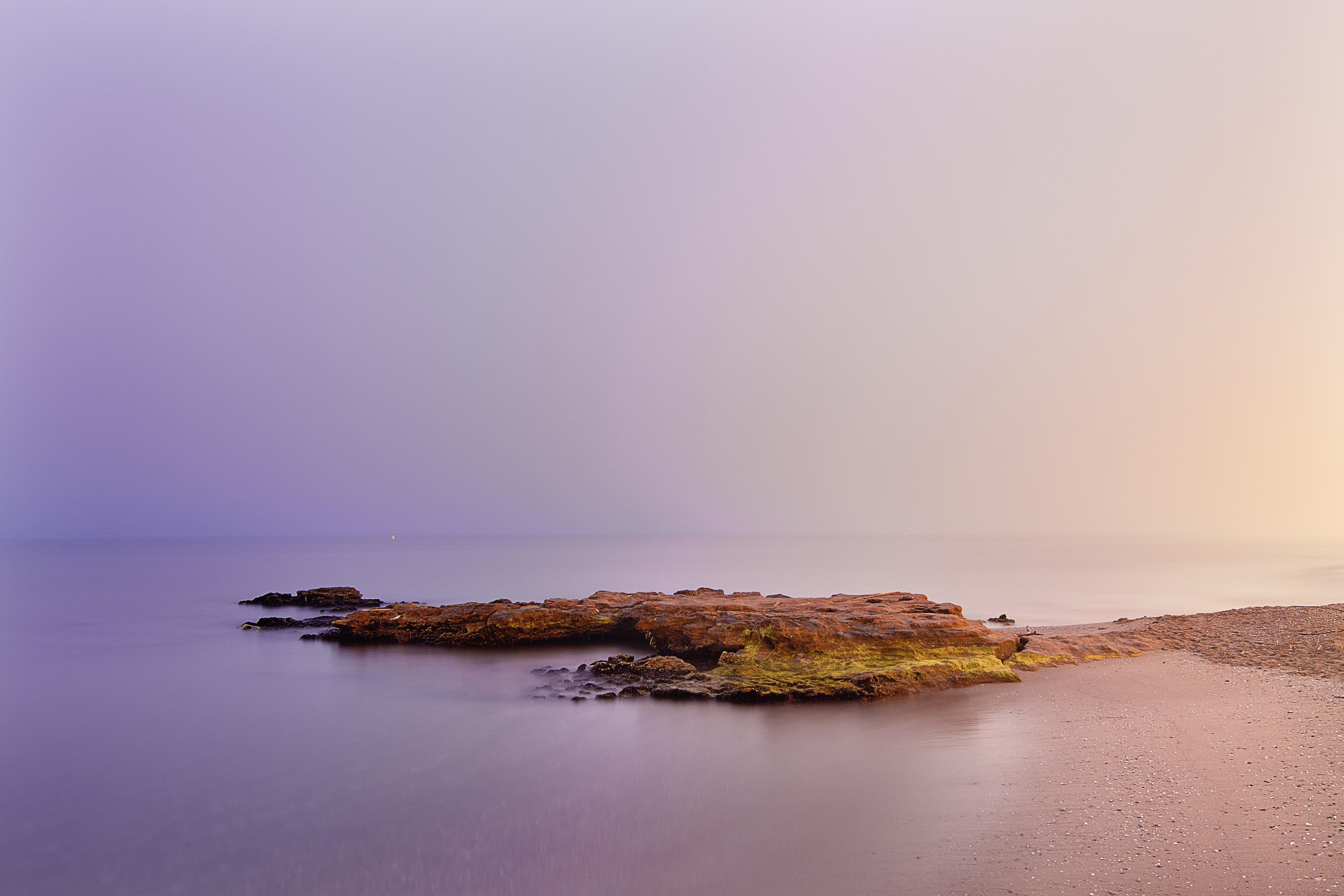 Purple sunrise beams over a rocky ocean formation in Playa de la Misericordia