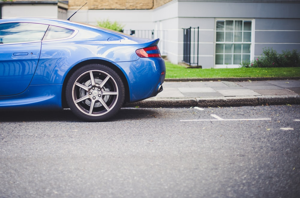 blue coupe parked in front of house