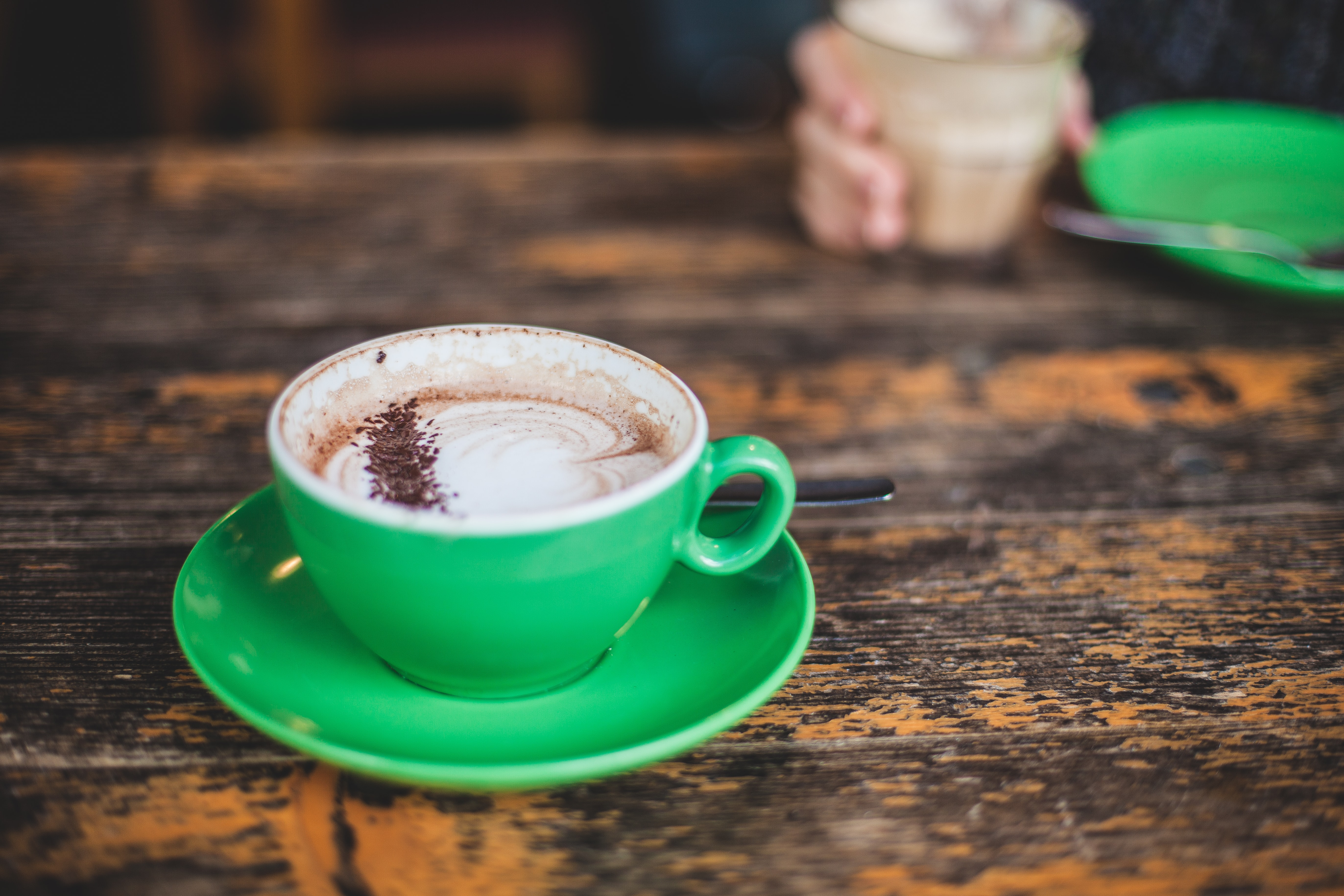 A latte in a green cup on a table with a person drinking their coffee on the other side
