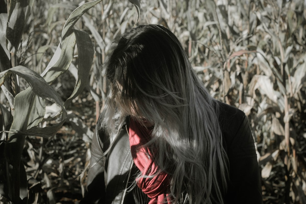 grayscale photo of woman standing beside corn field