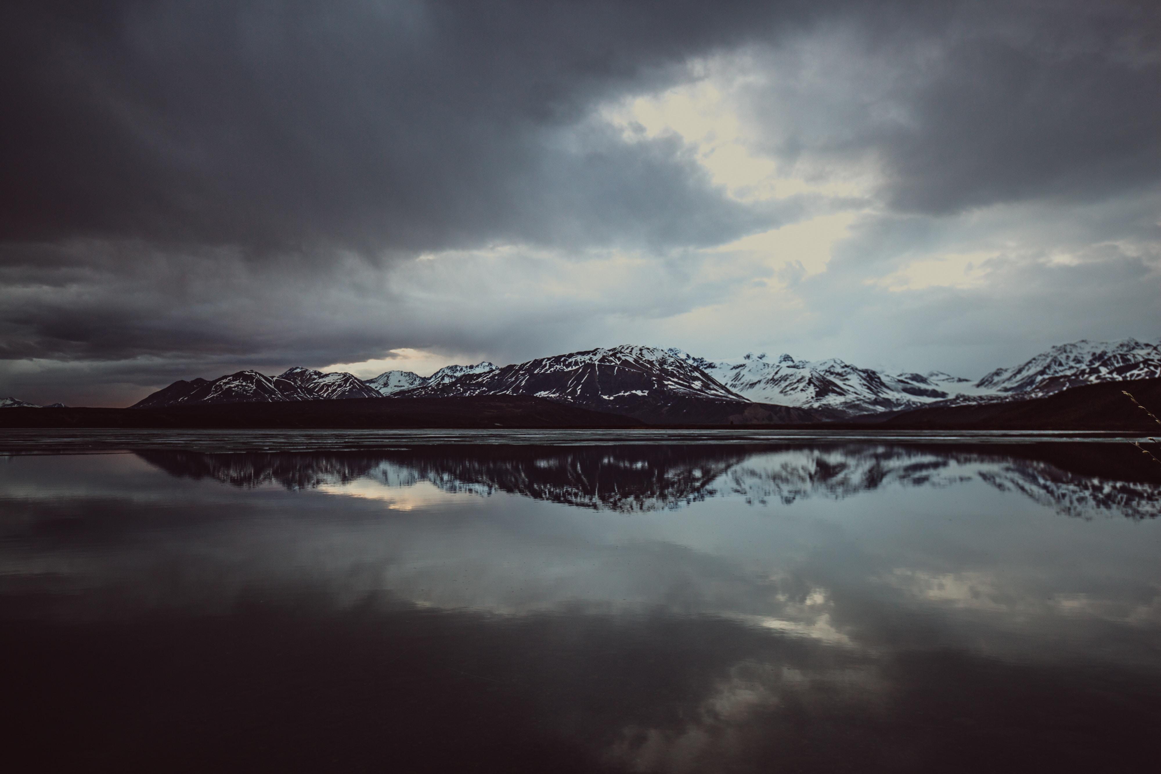 A snowcapped mountain range reflecting against Paxson Lake