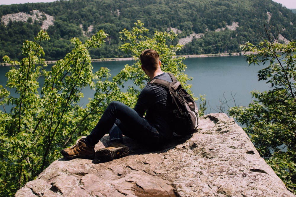 person with backpack sitting on gray rock