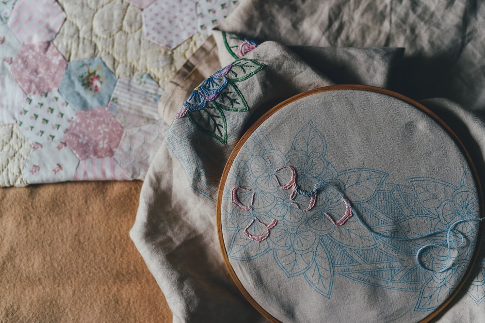 An incompleted needlepoint in a hoop laying on top of a quilt