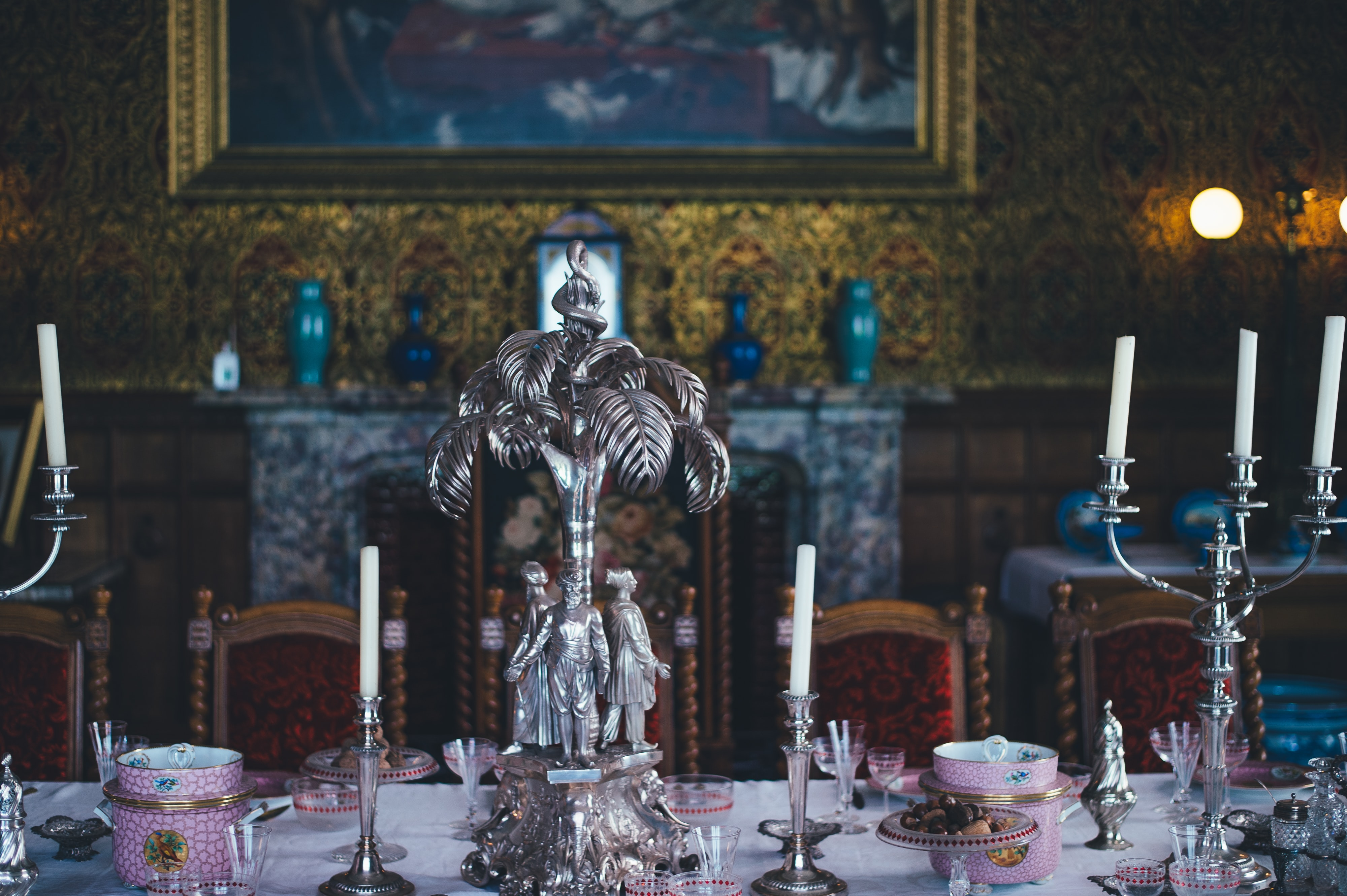A set table with ornate silver candlesticks and elegant tableware in a Victorian interior