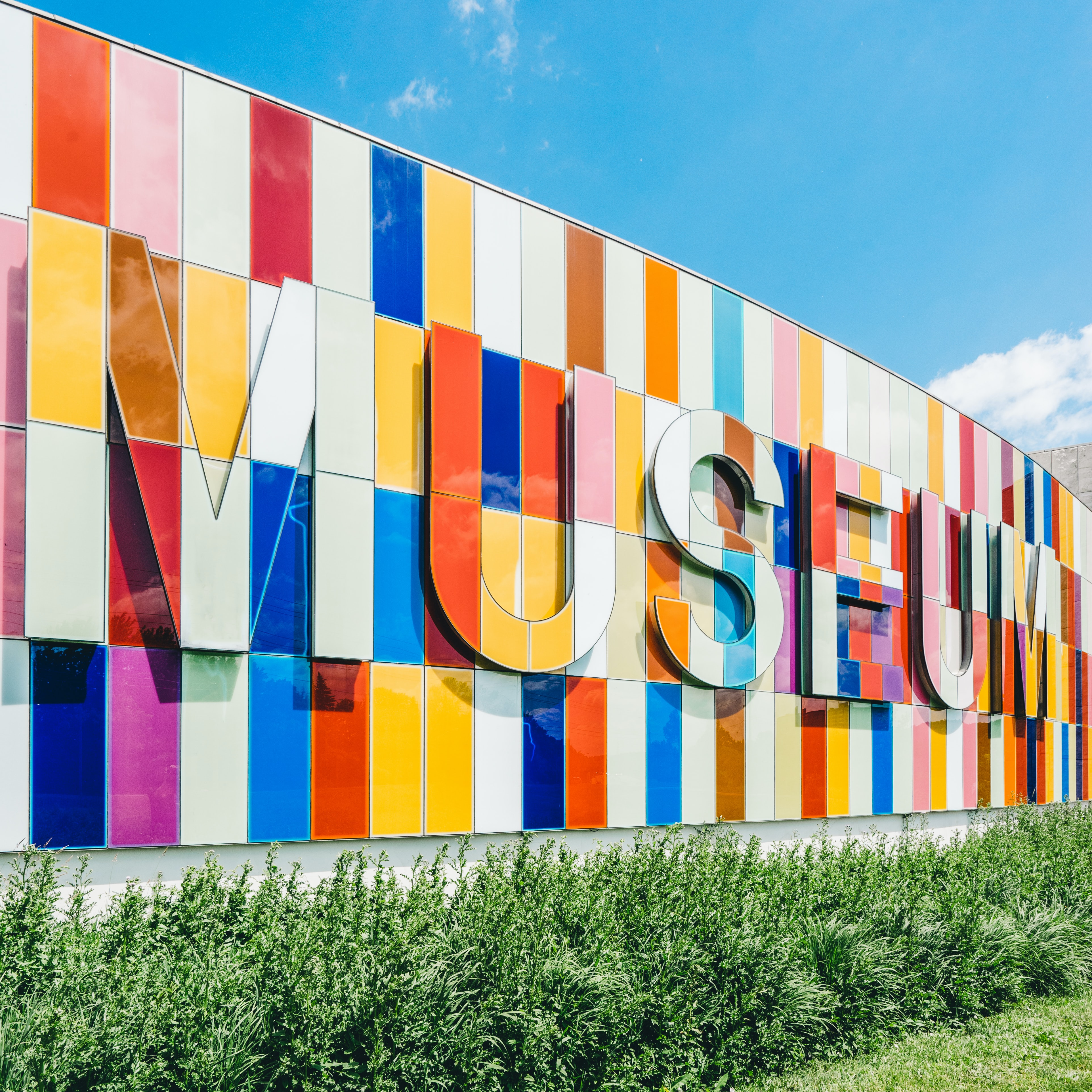 Colorful tile sign of museum typography text sign near grass with blue sky, Waterloo Region Museum