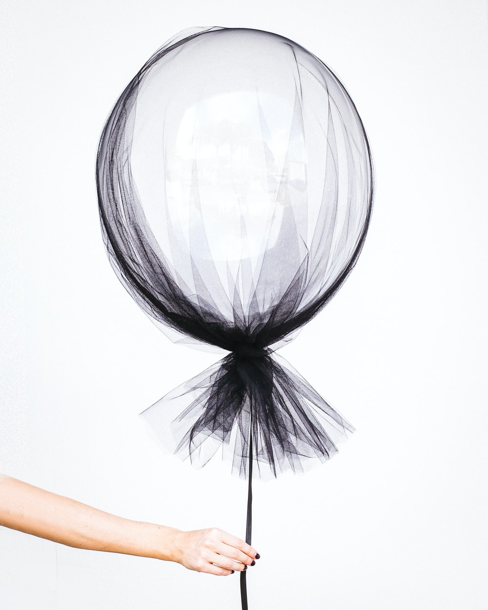 person holding black balloon decal
