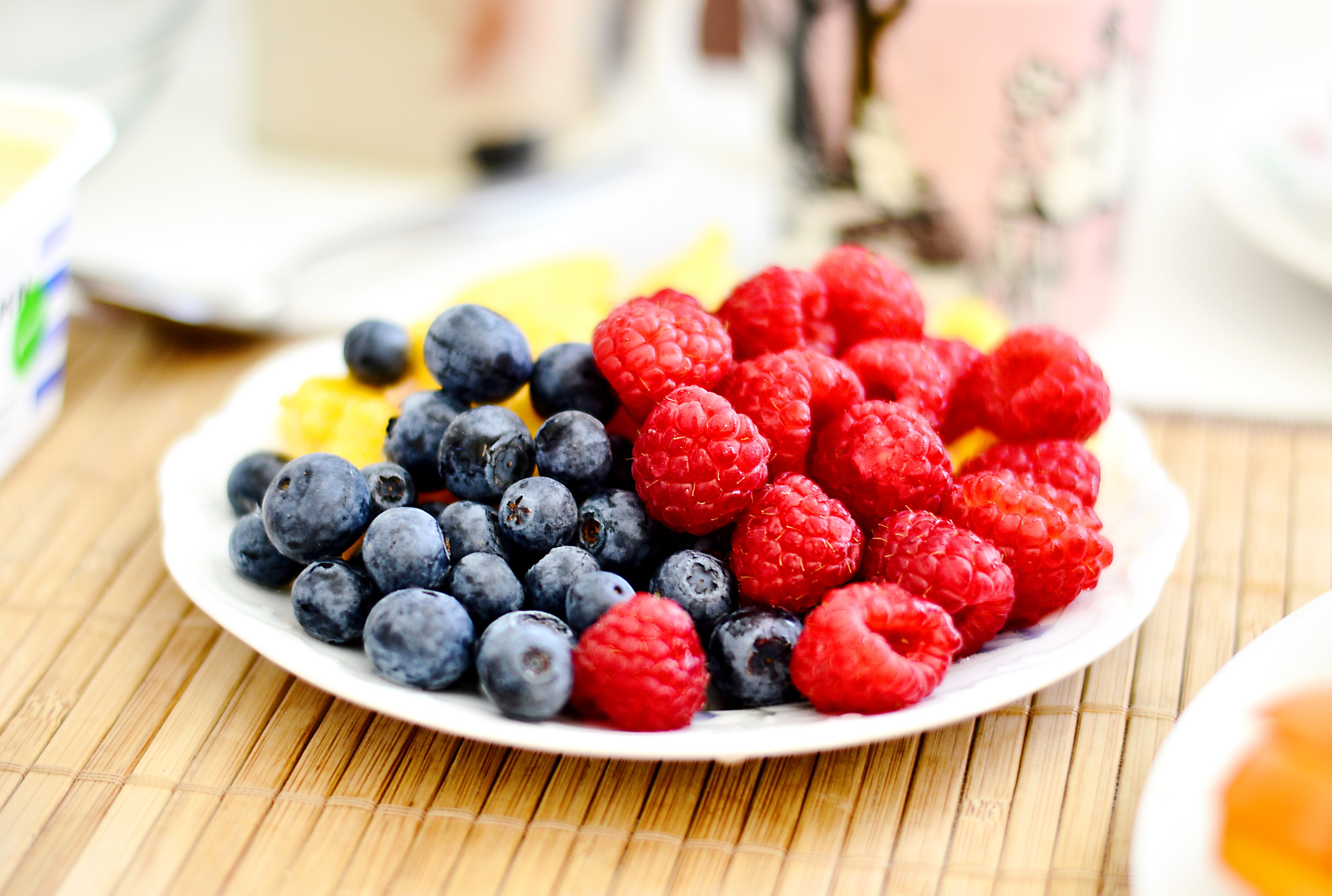 Plate of fresh fruit with raspberries and blueberries on a picnic table