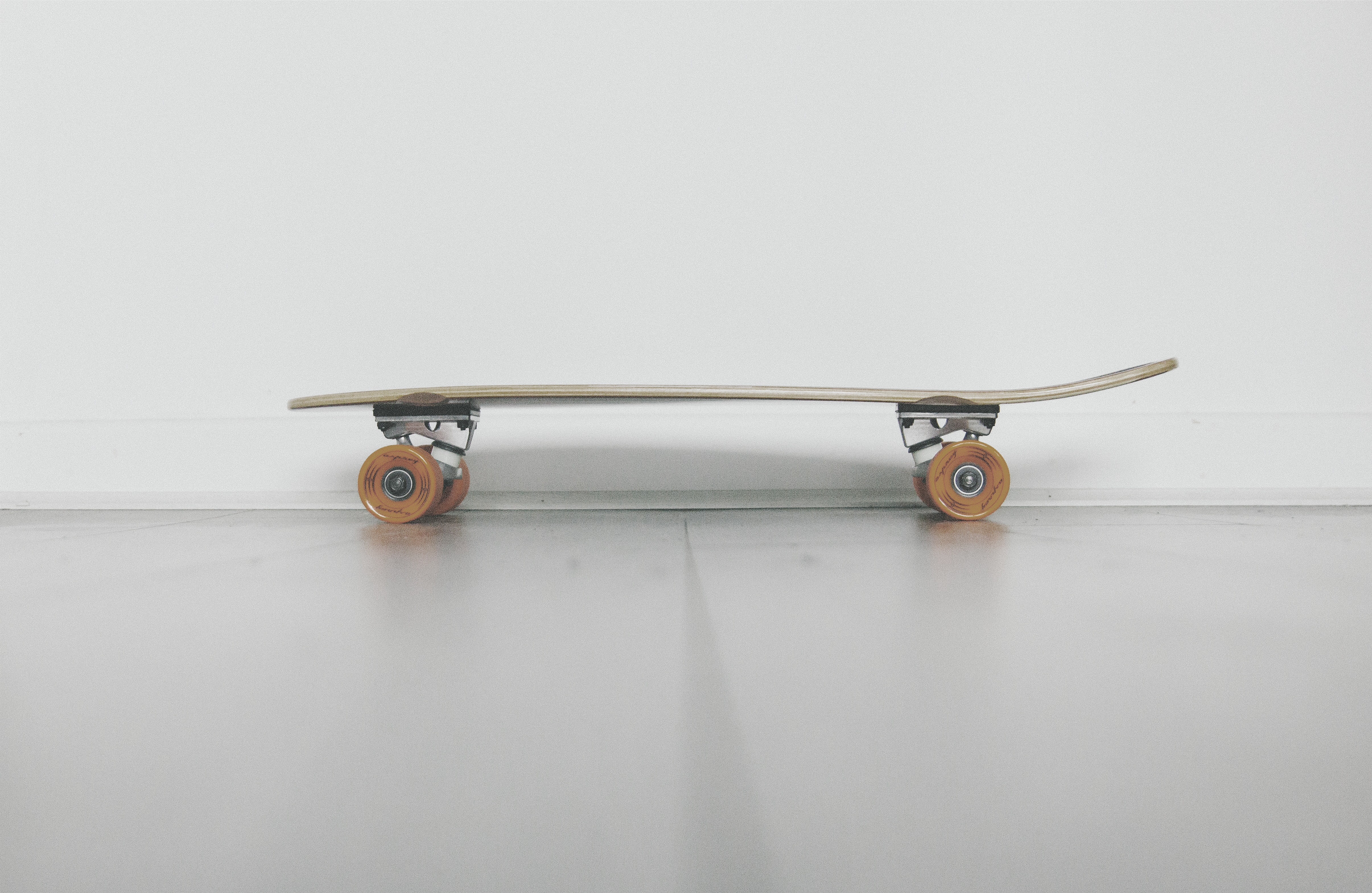 A low shot of a skateboard near a white wall