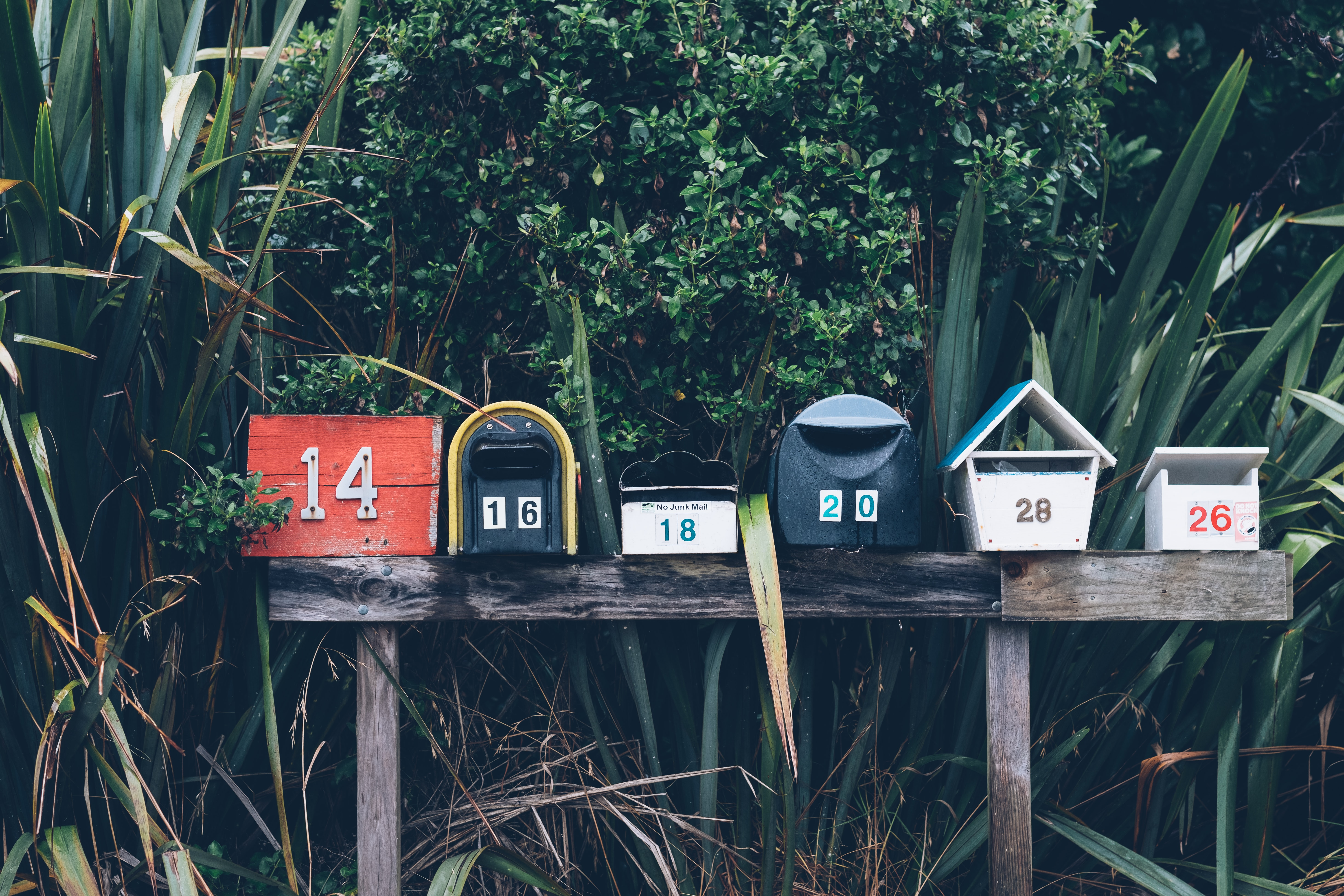Several mailboxes on a post surrounded by