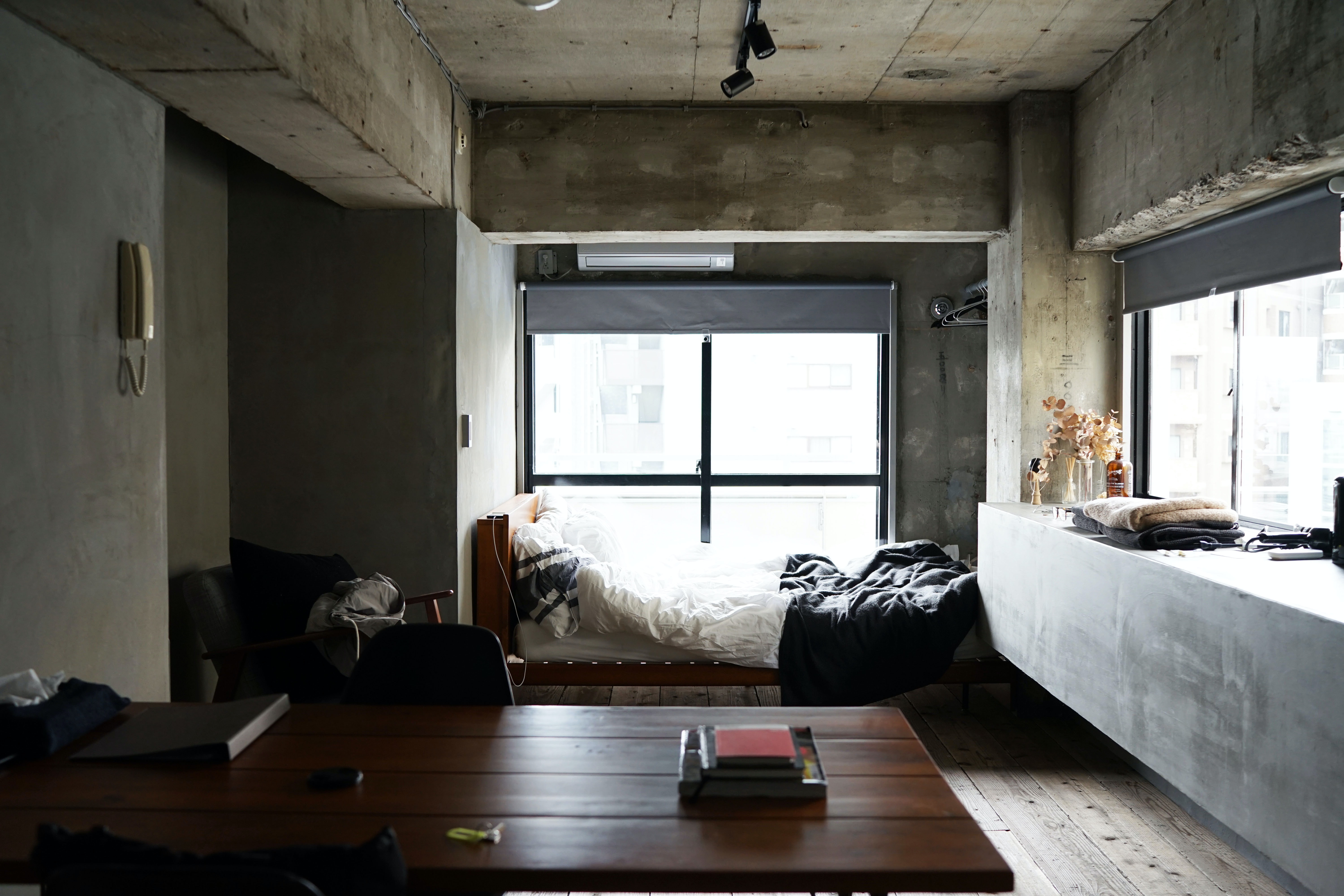 A small bedroom with a bed, table, chair, phone, and windows in Shibuya