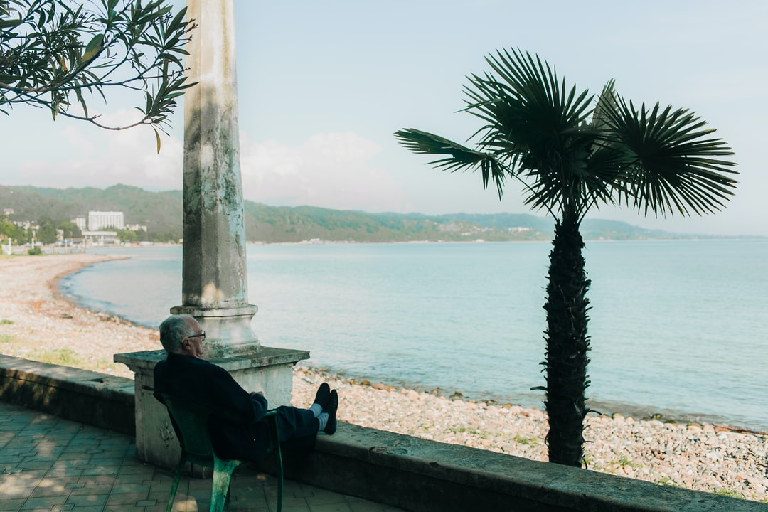 An old man sitting on a chair with his feet on a ledge, looking out into the sea in Sokhumi