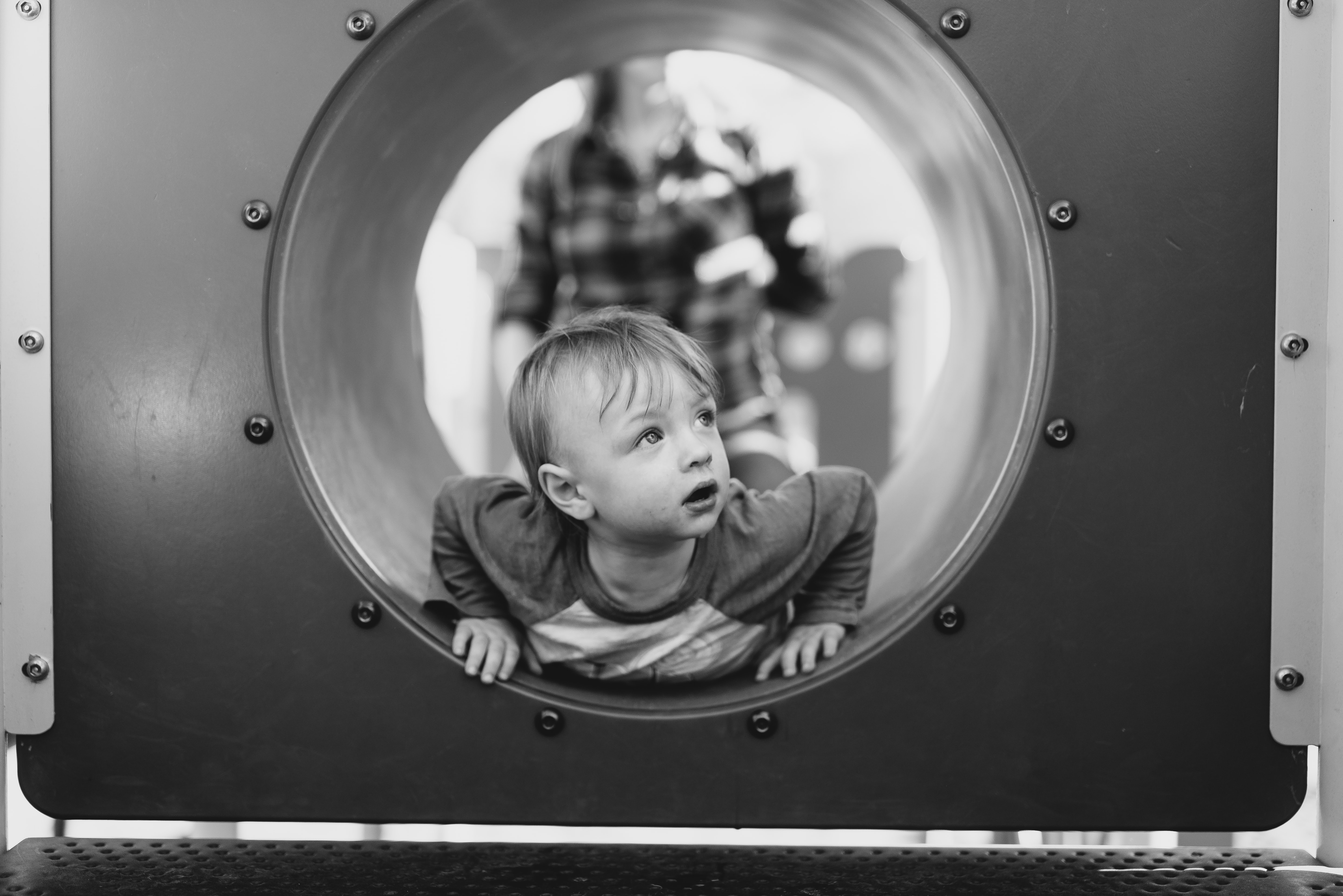 grayscale photo of child in hole