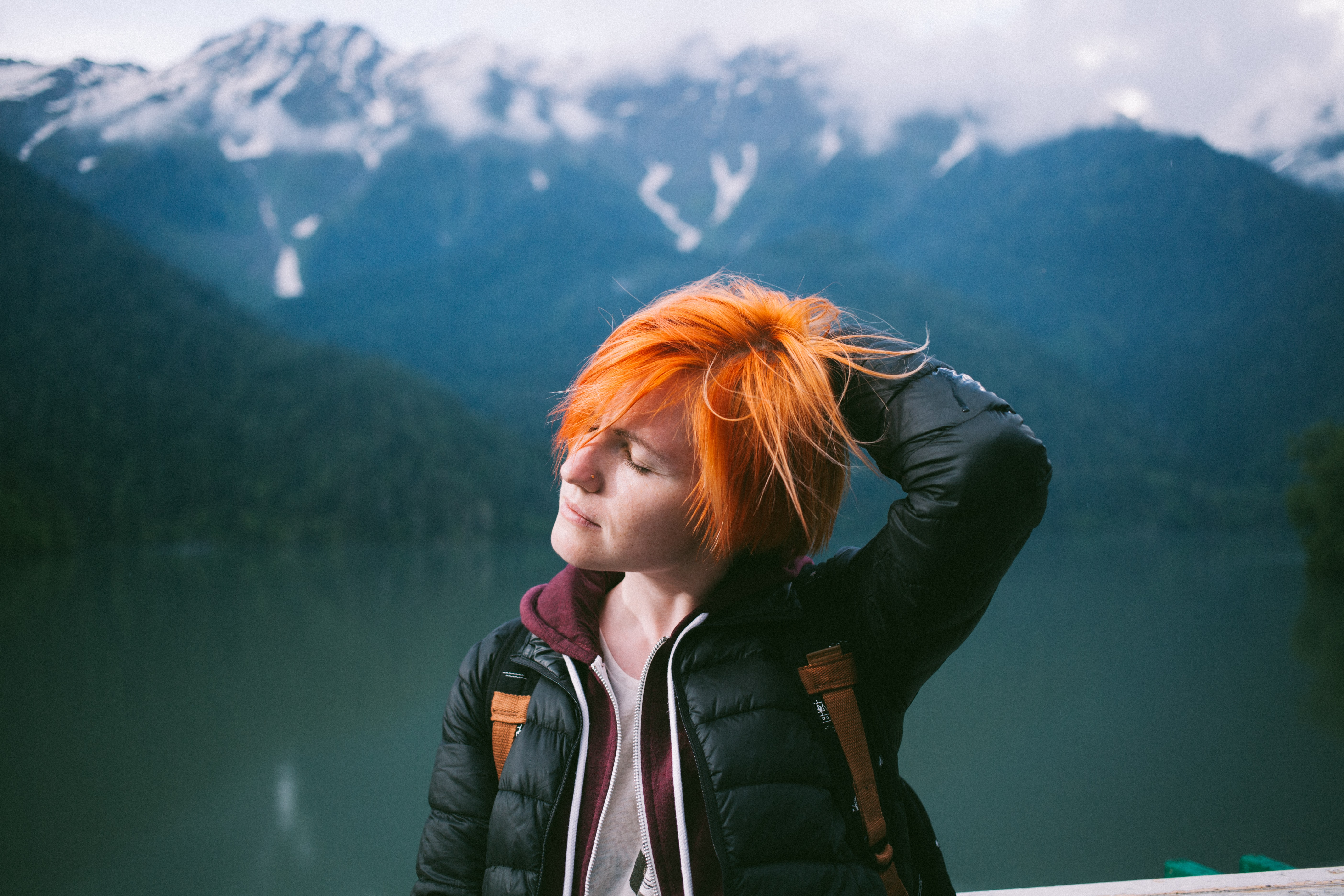 A woman closes her eyes and places a hand in her orange hair in the mountains