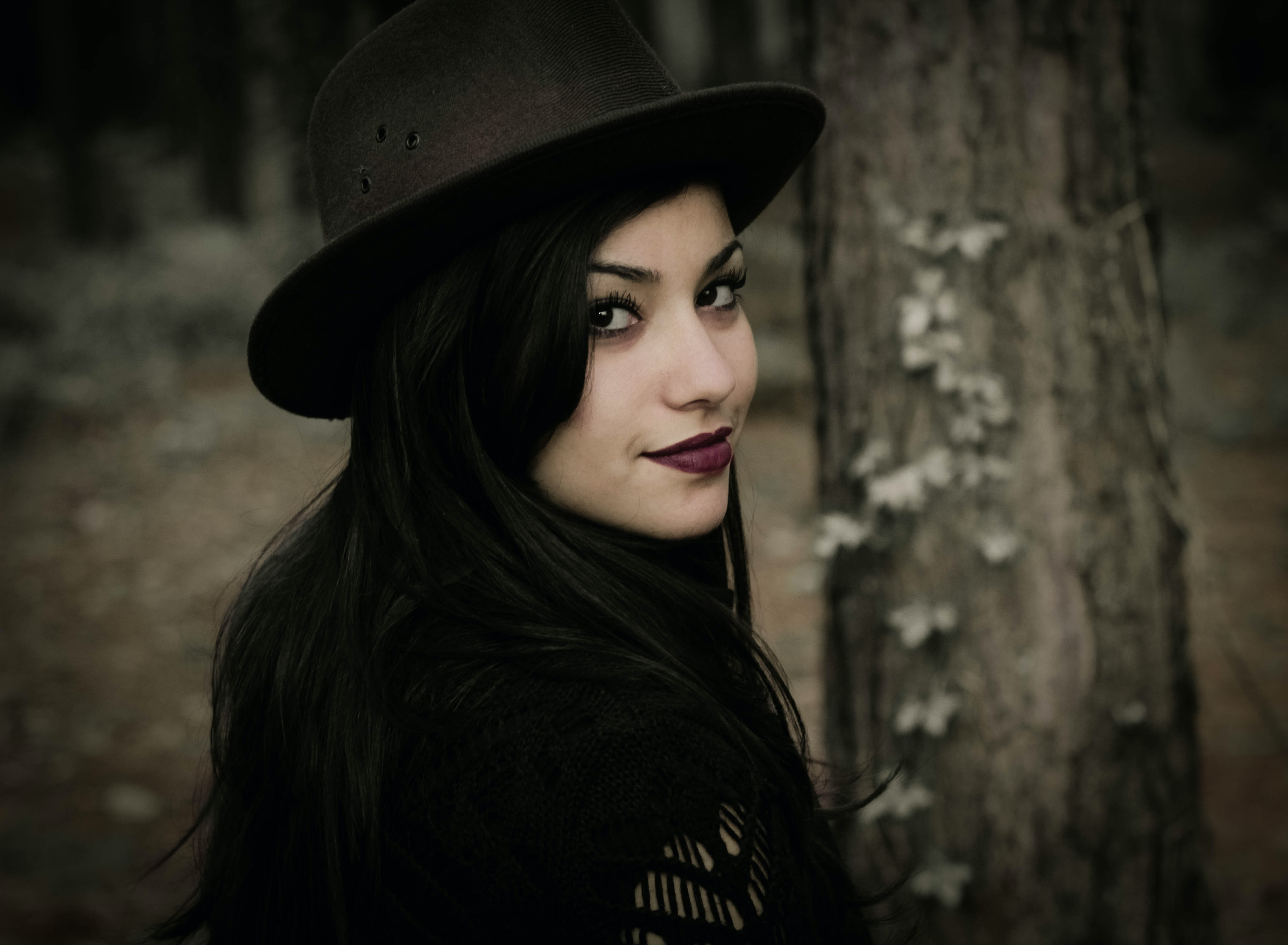 A dark-haired woman in a hat smiling near a tree