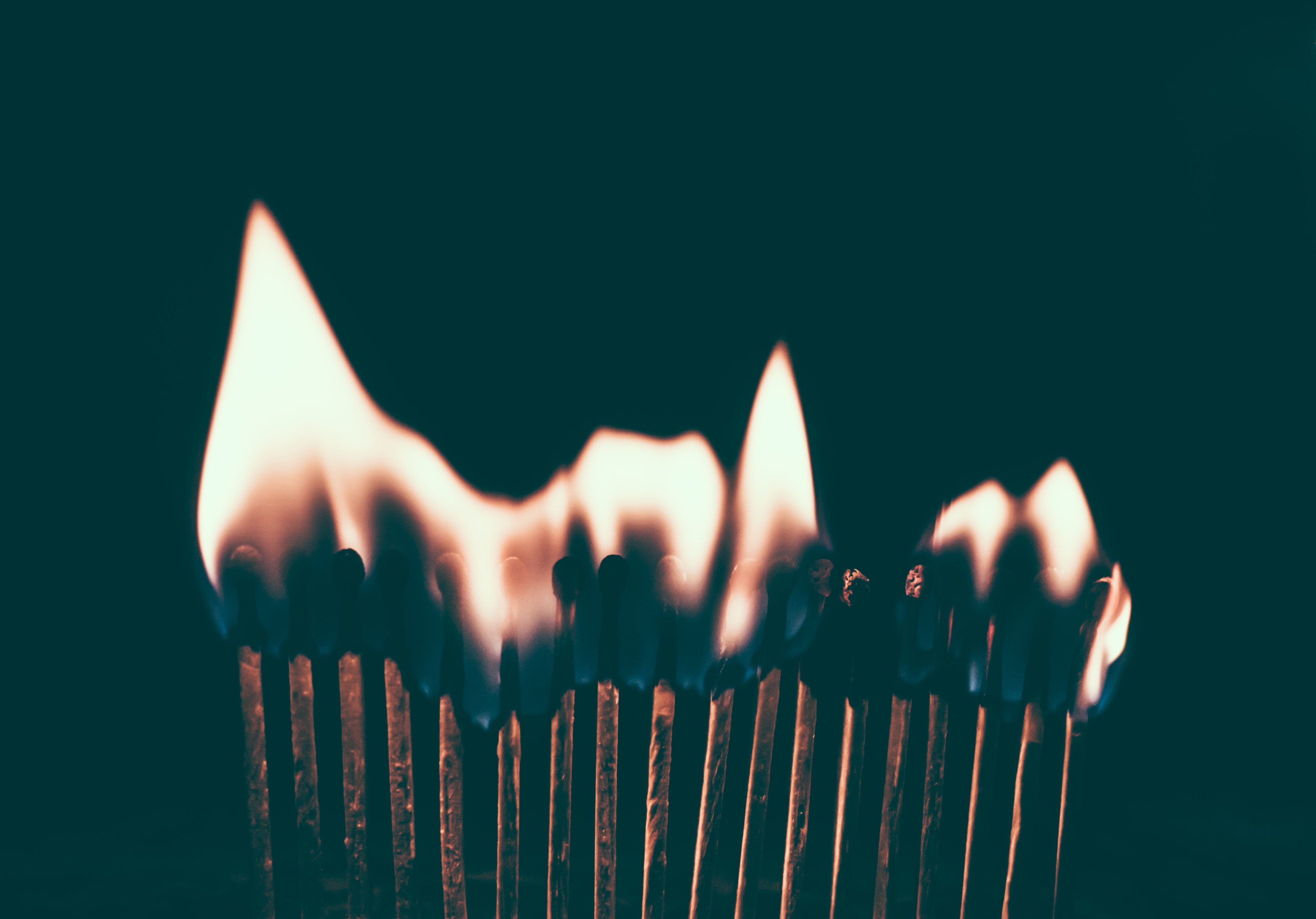 Flames ignite on a line of burning matches in the dark