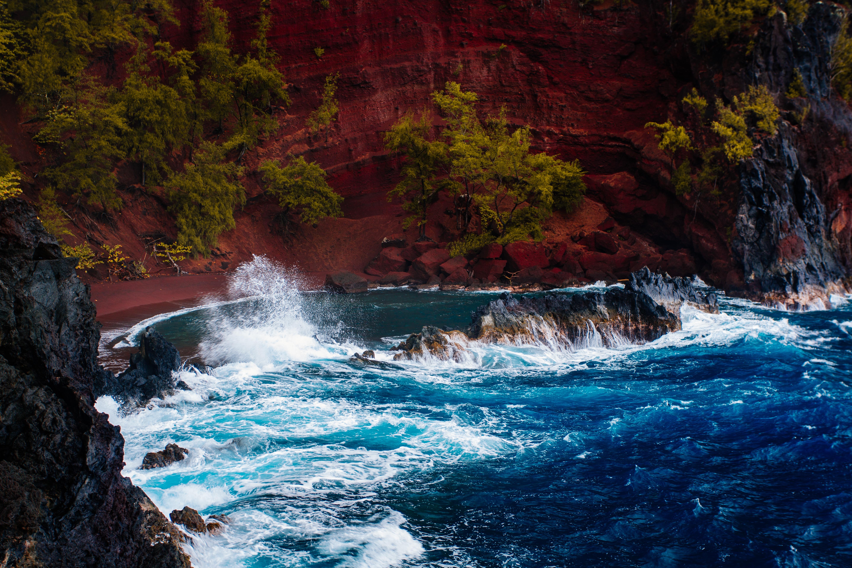 Rough sea splashing rocks in front of red sand ocean bay at Hana