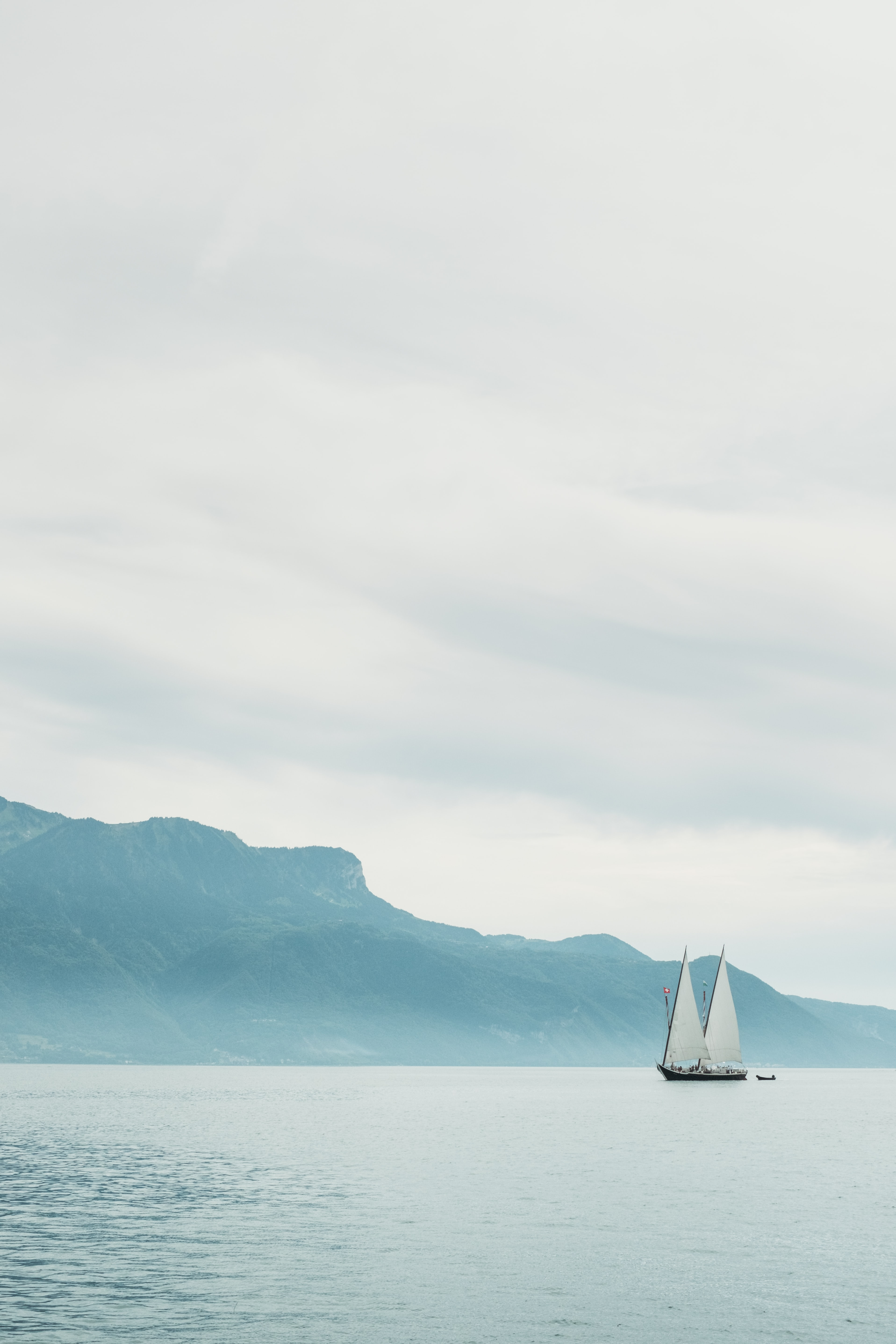 A sailboat floating in the water near a large mountain.