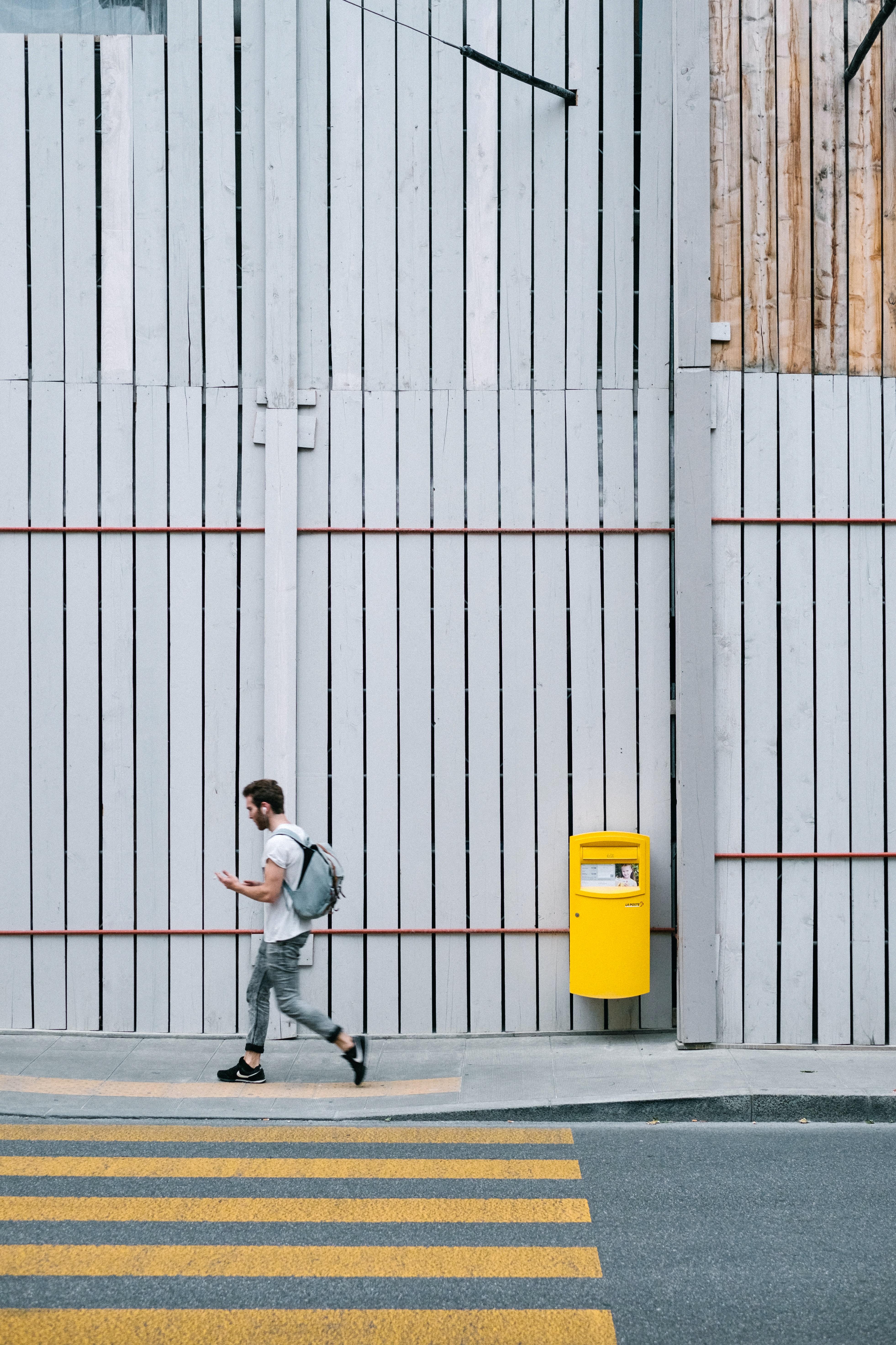 man walking on sidewalk beside pedestrian lane at daytime