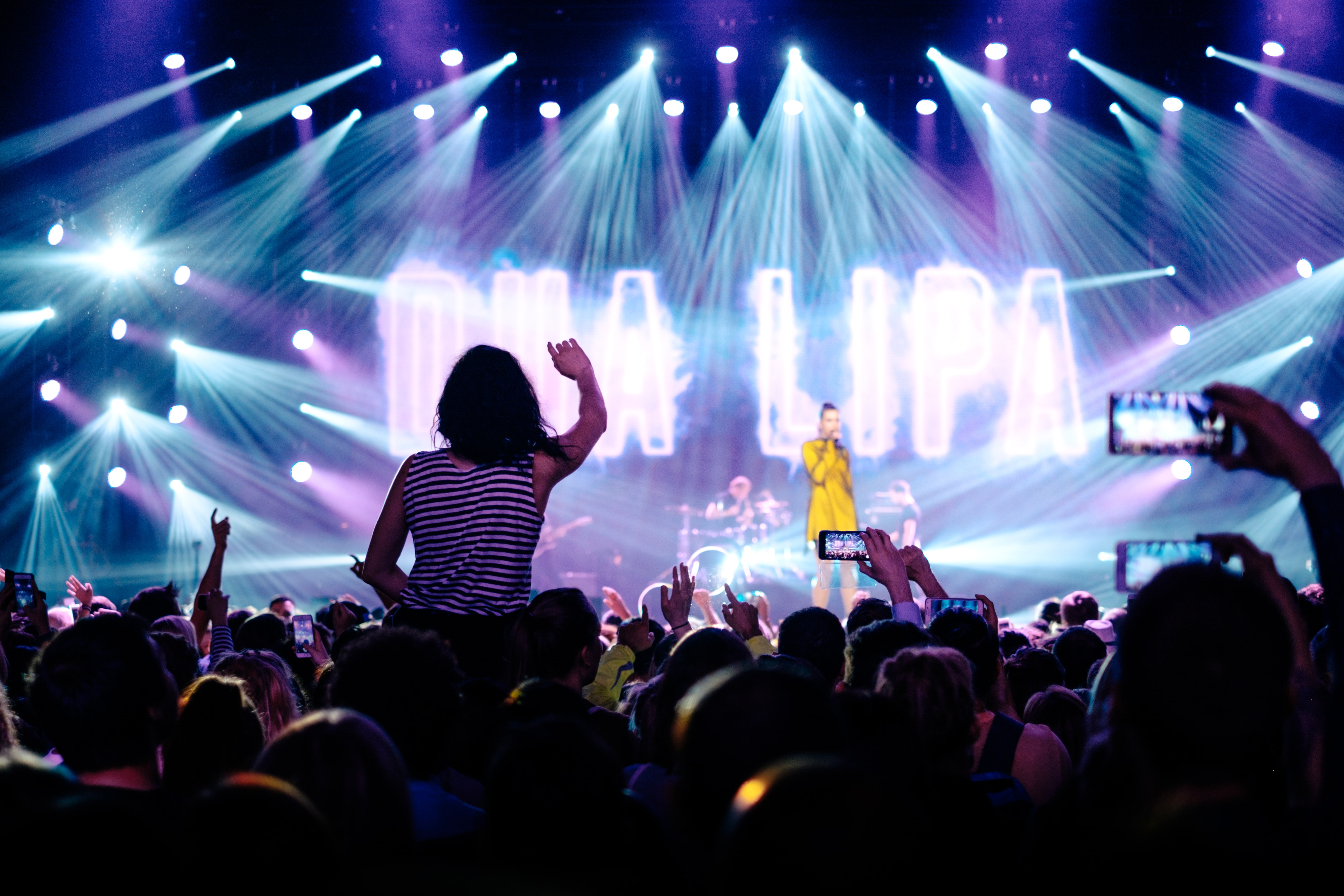 Concert audience lifting up their hands and phones as a woman in a yellow dress performs on stage