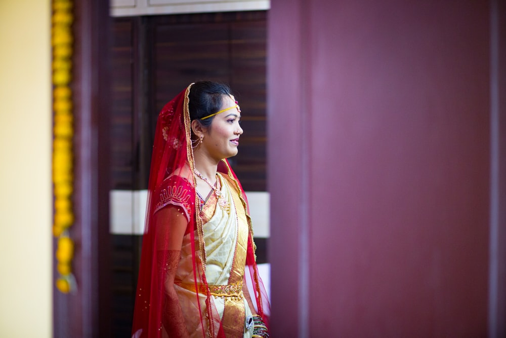 woman in sari dress standing near purple wall