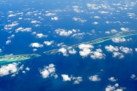 aerial photography of green island and clouds