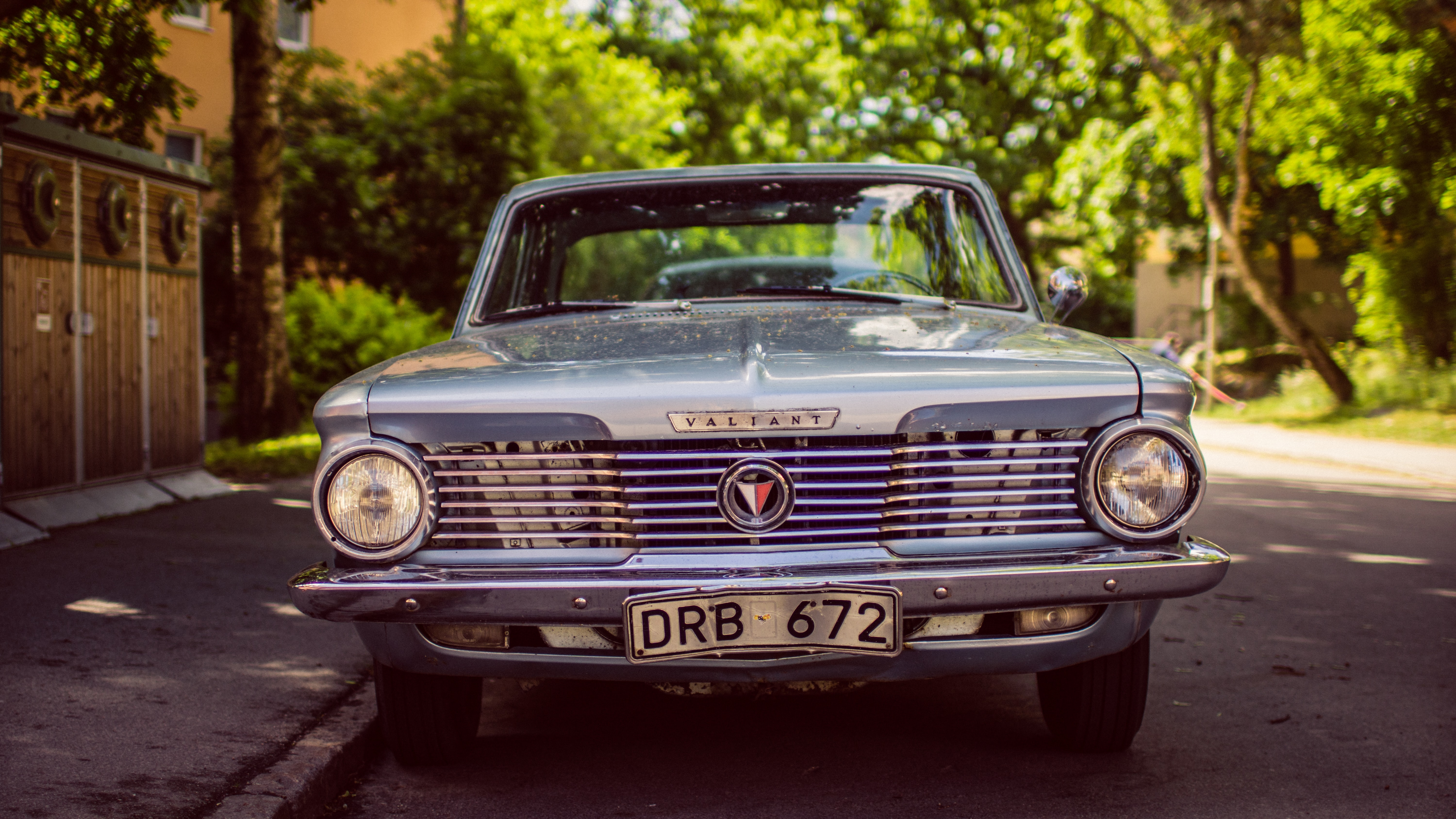 Vintage, blue Valiant with shiny silver grille parked on the sidewalk in front of trees