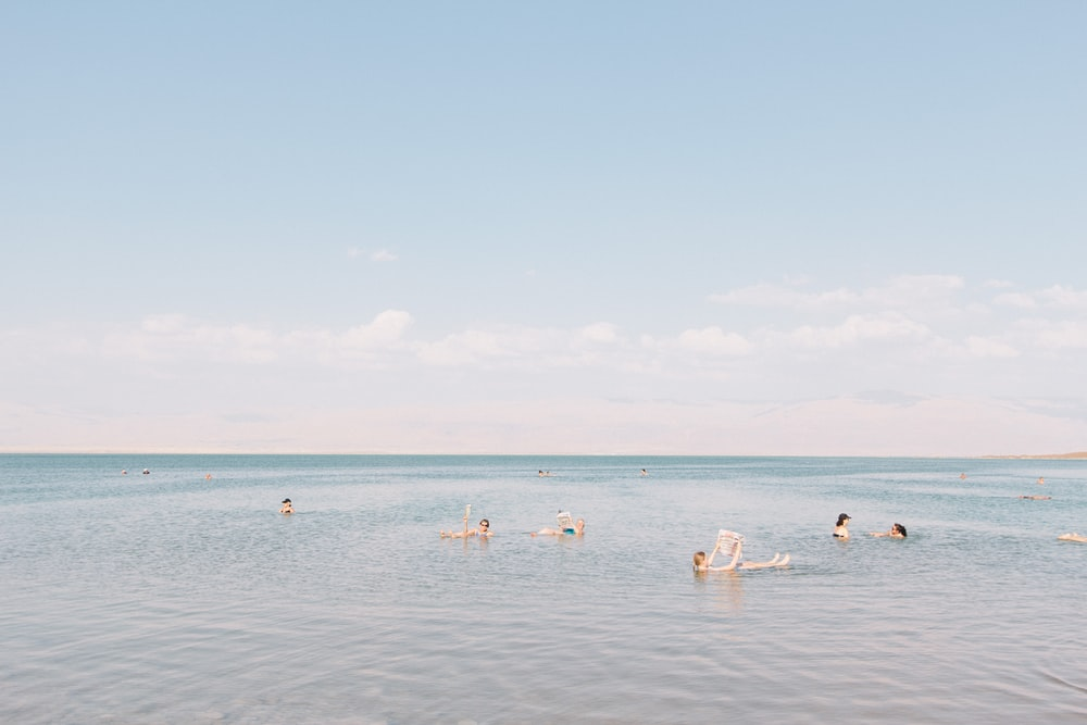 people swimming on sea under cloudy sky