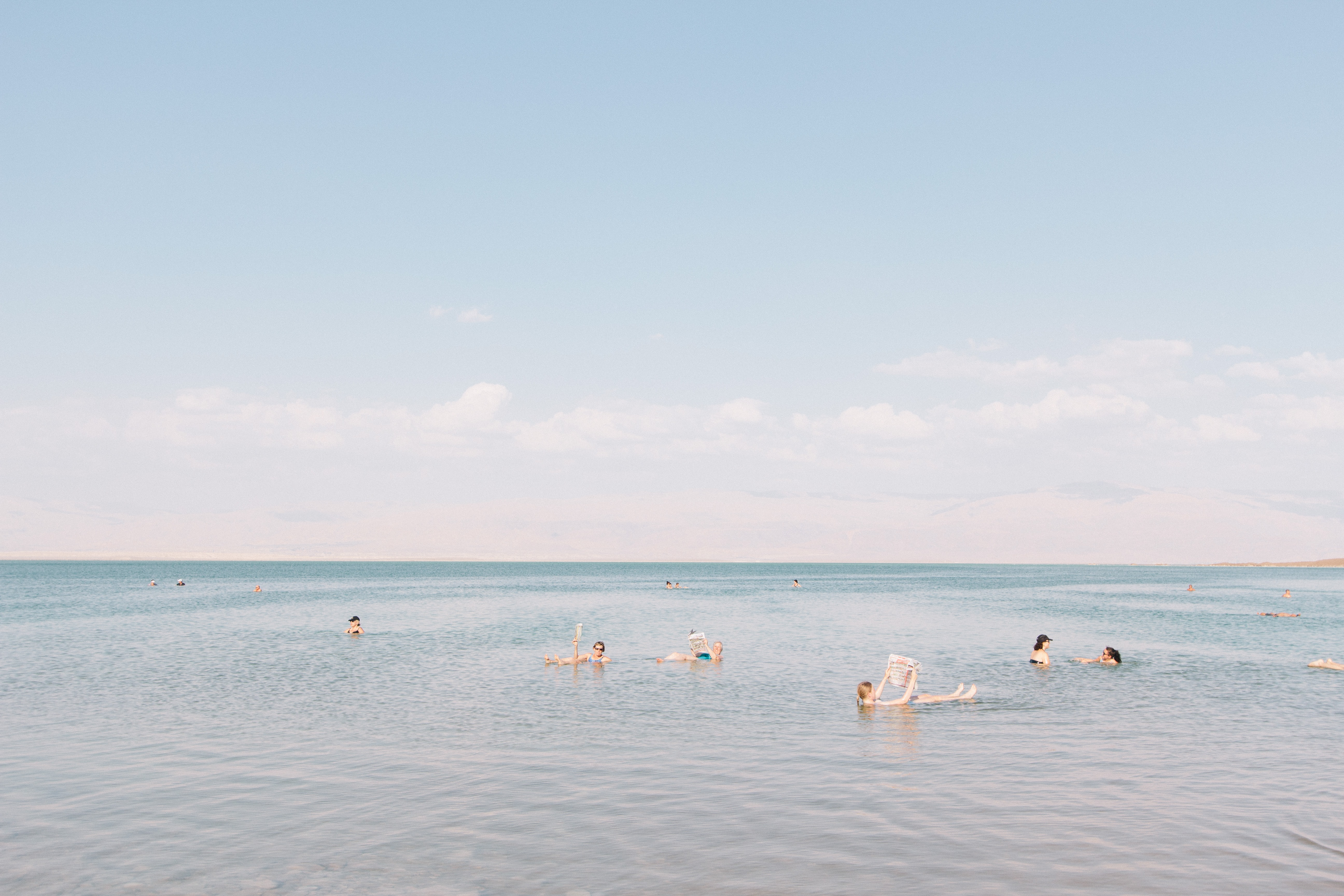 People floating in the very salty water in the Dead Sea