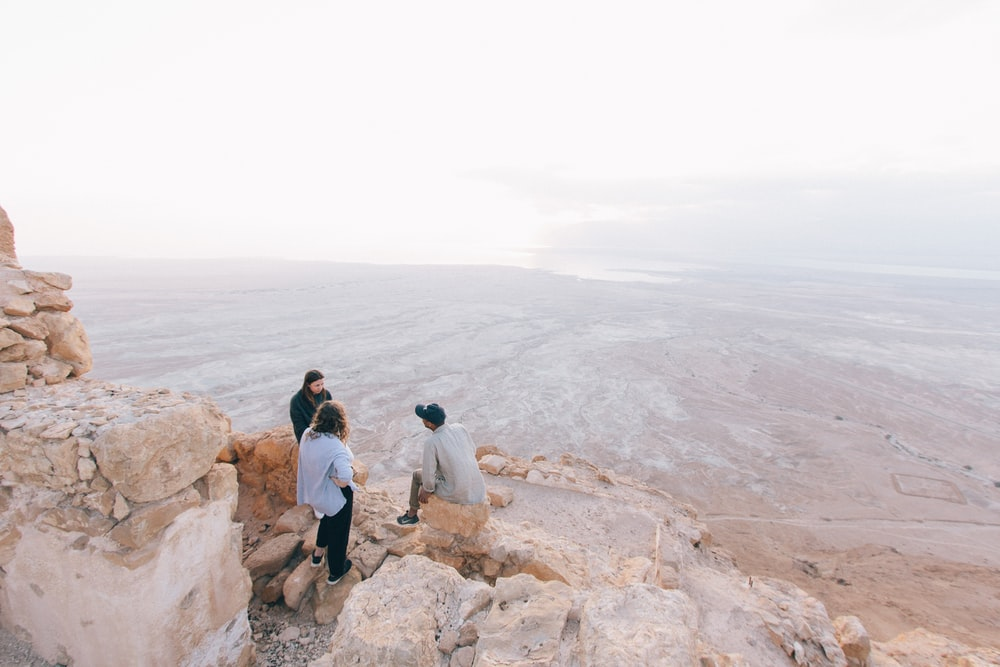 three person on cliff under white sky
