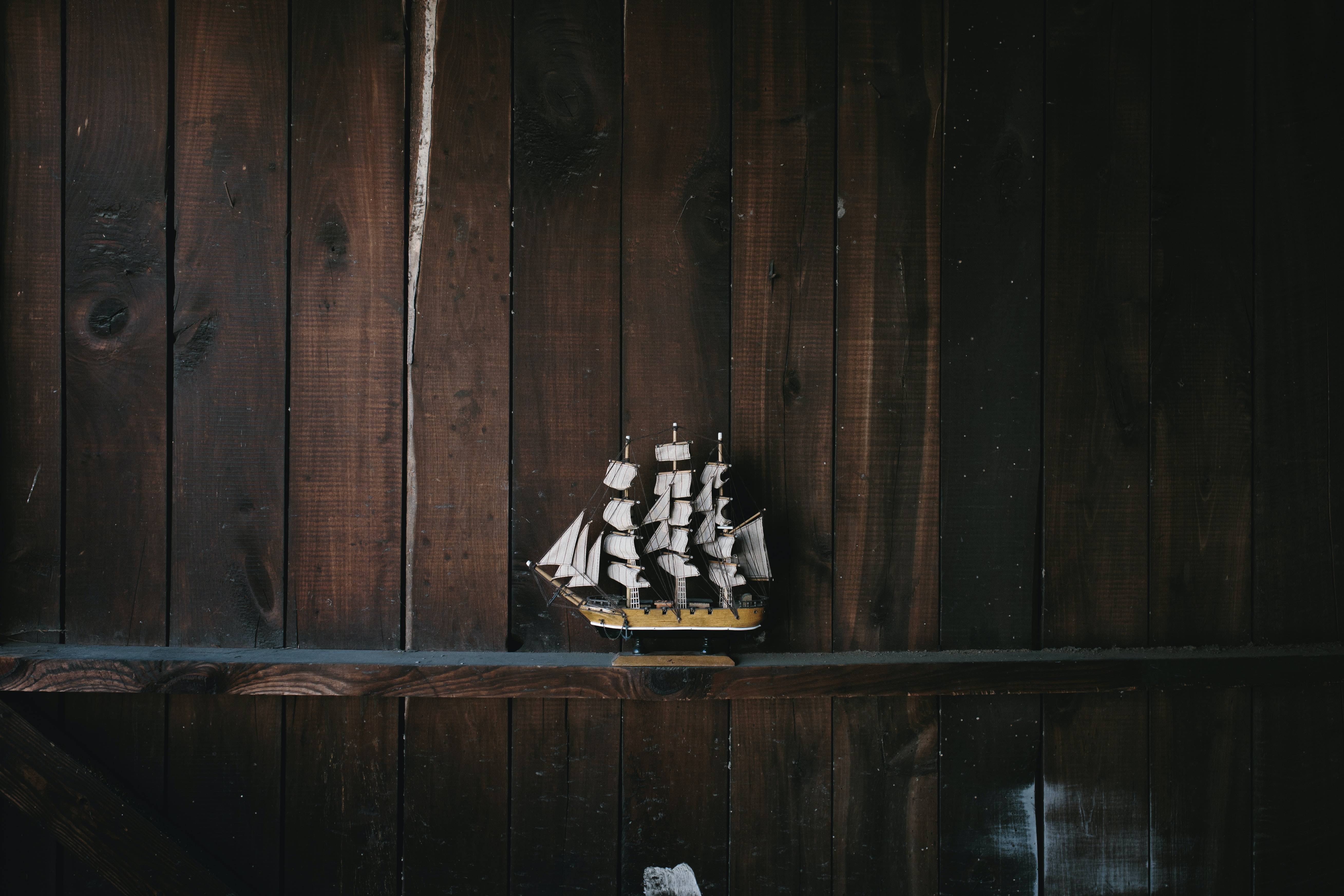 black, brown, and white galleon ship scale model on brown wooden shelf