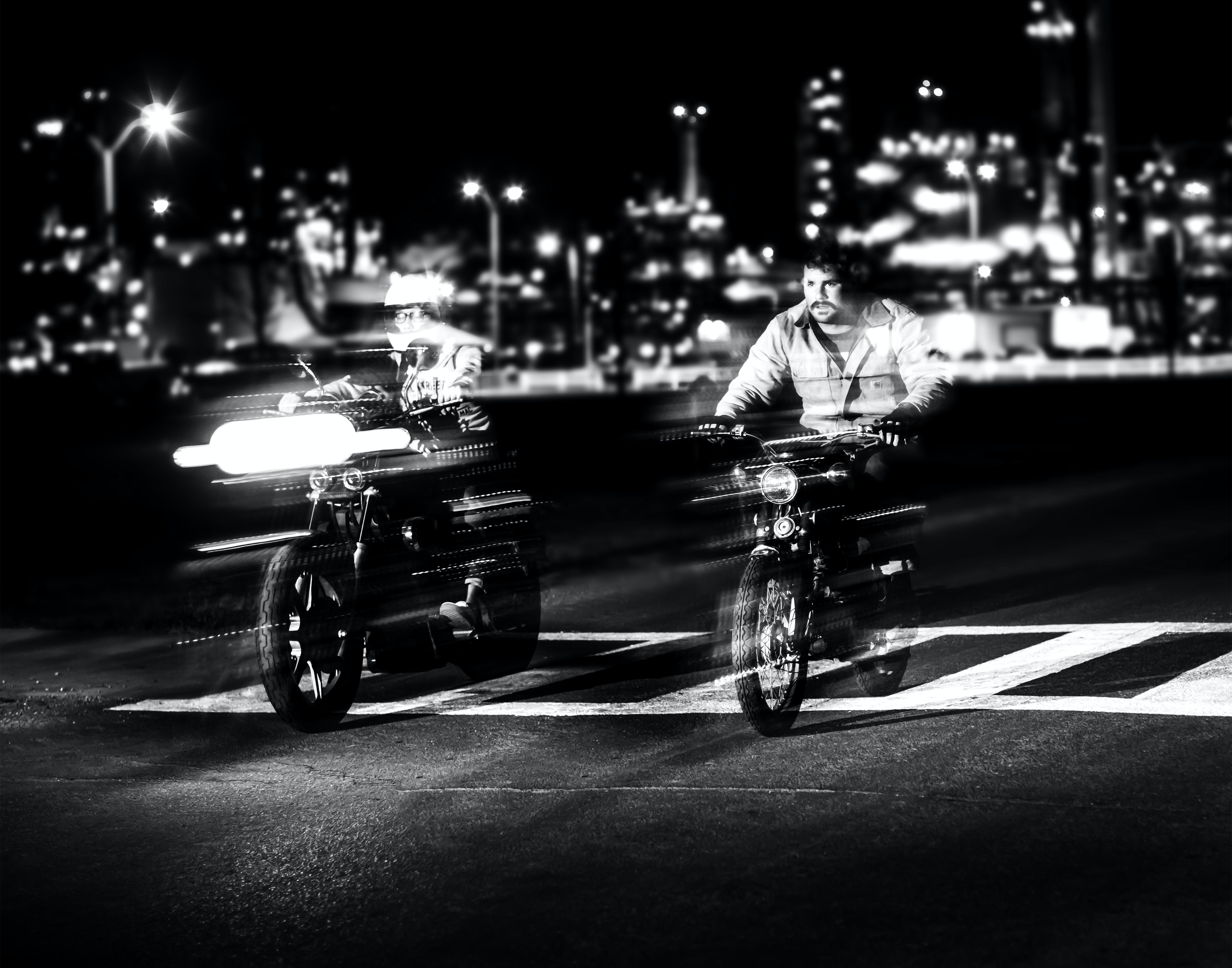 Black and white motion shot of people riding motorbikes on road at night