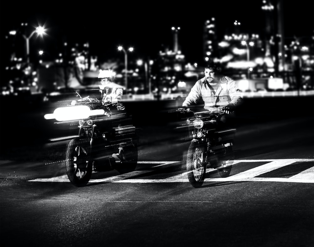 grayscale photo of person riding motorcycle near building and street lights